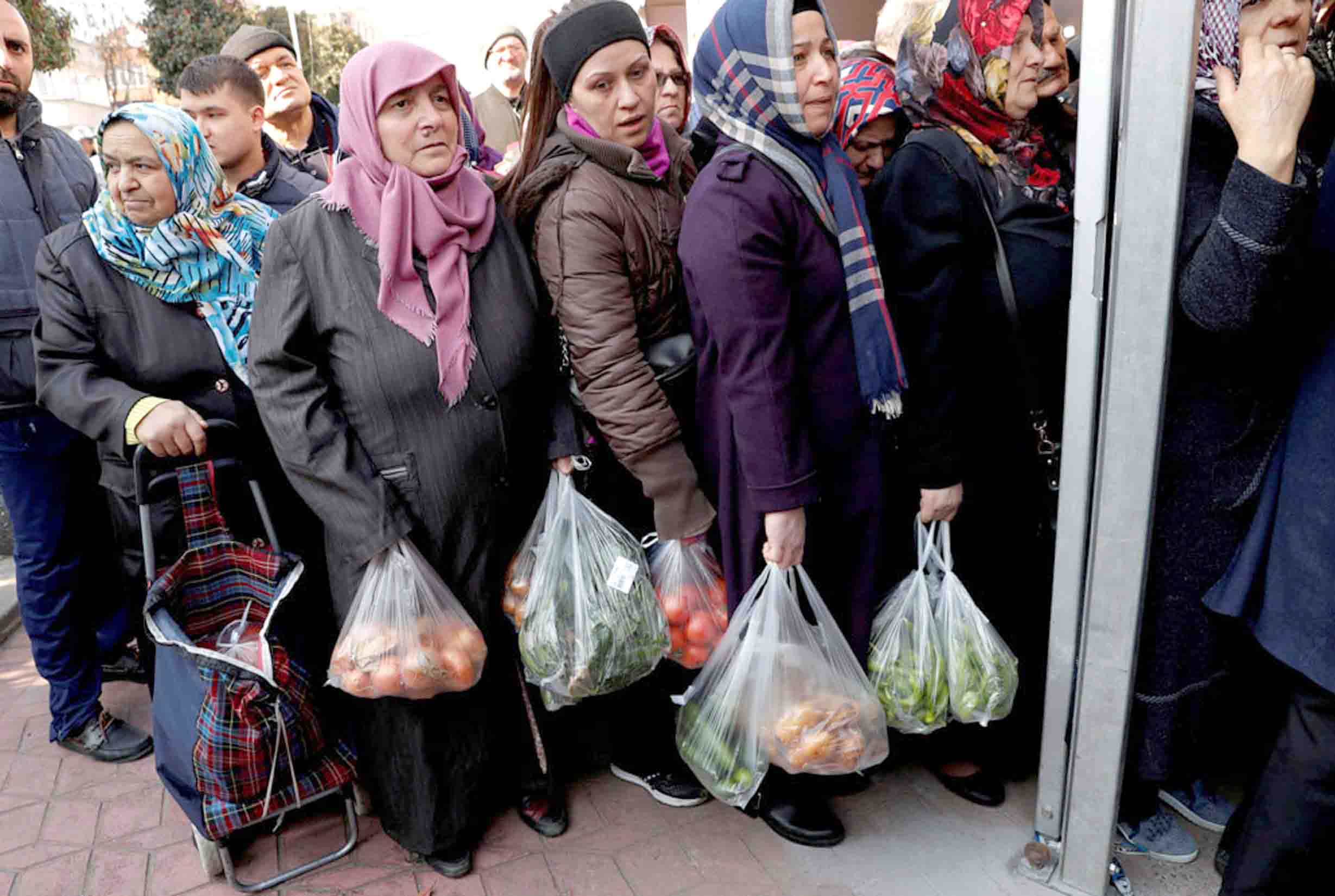 People wait in line to buy vegetables sold in a tent set up by the municipality in the Bayrampasa district of Istanbul, Turkey, February. (Reuters)