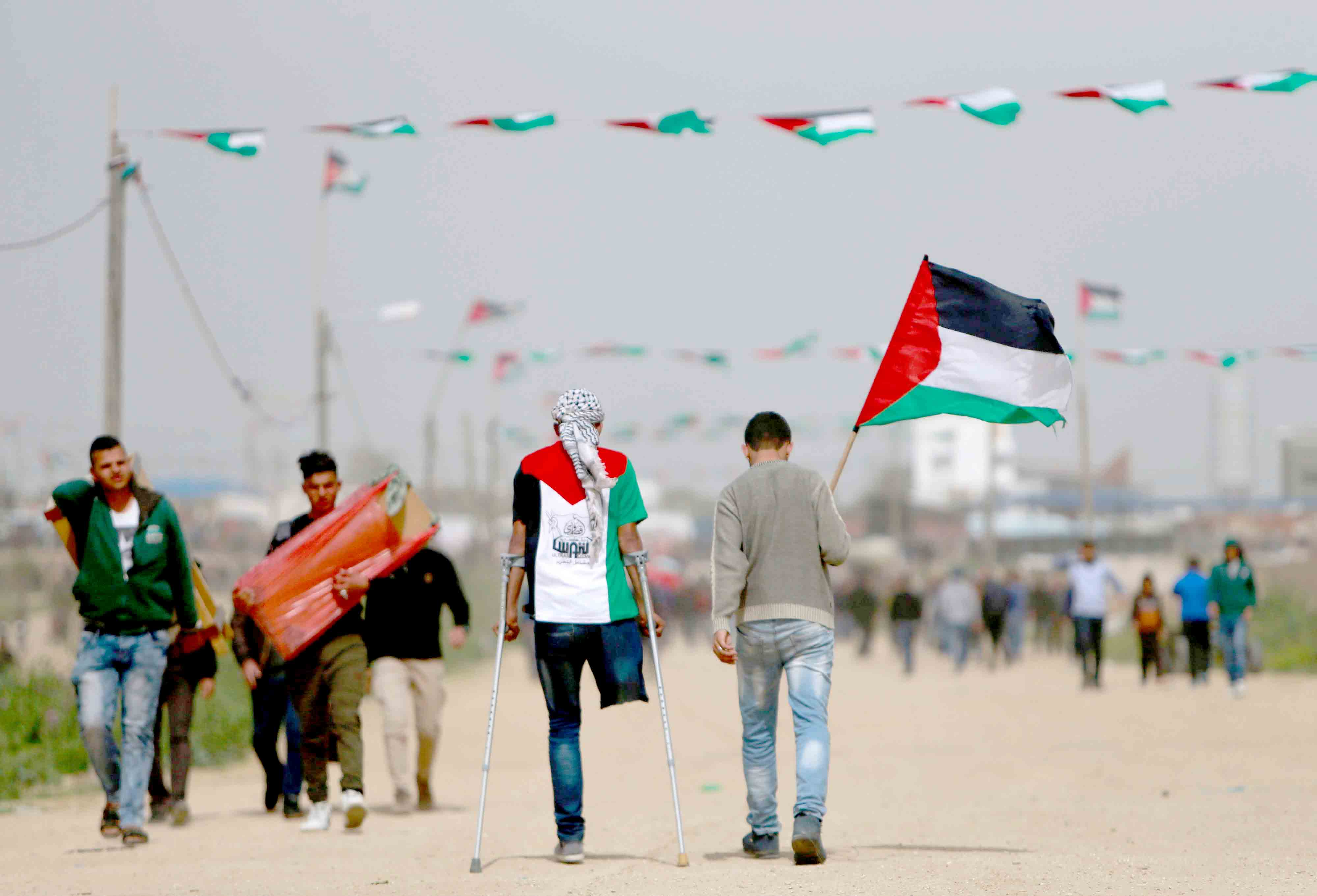 Limited options. A Palestinian man wearing a t-shirt depicting the colours of the Palestinian flag walks on crutches with another holding a national flag as they head towards a demonstration near the border with Israel, March 30. (AFP)