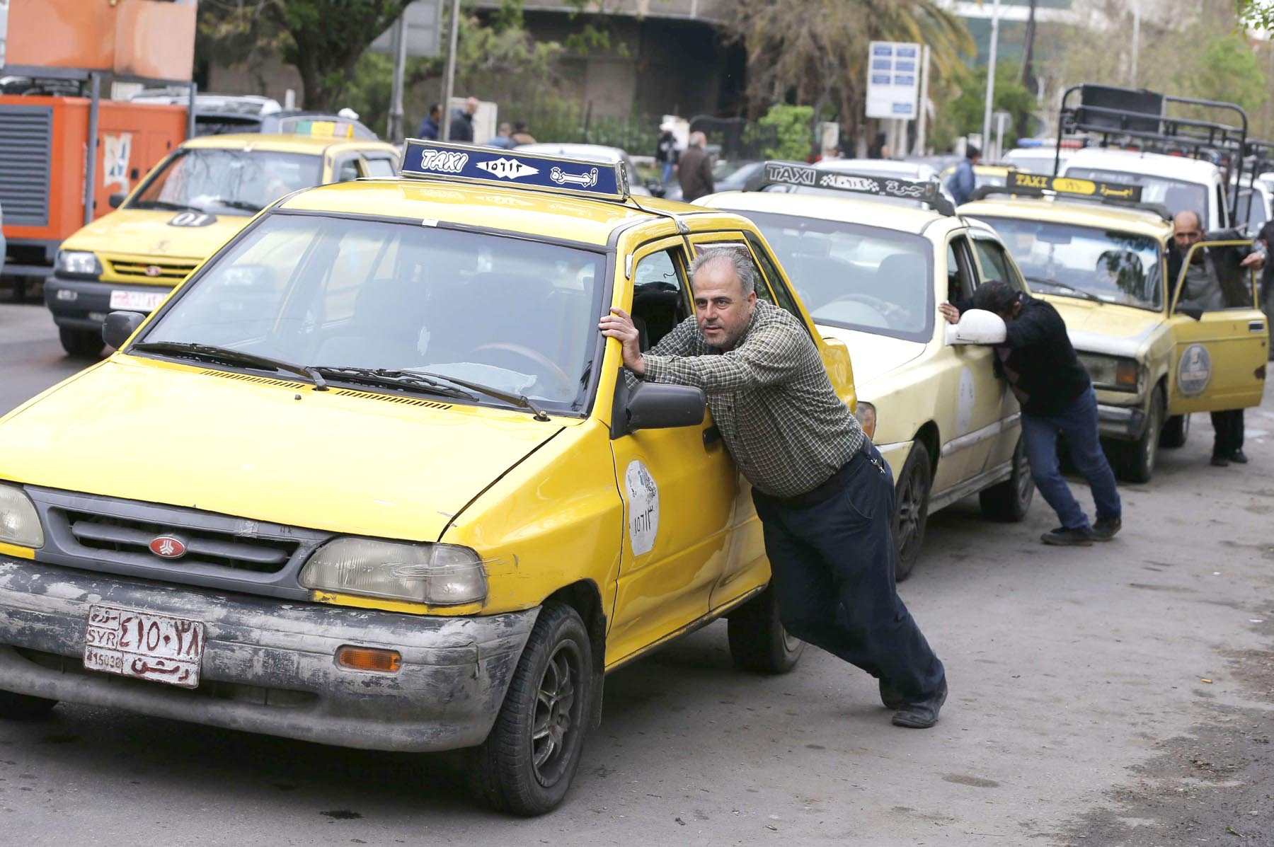 At a standstill. Taxi drivers push their cars that ran out of fuel to a petrol station in Damascus, April 16.    (AFP)