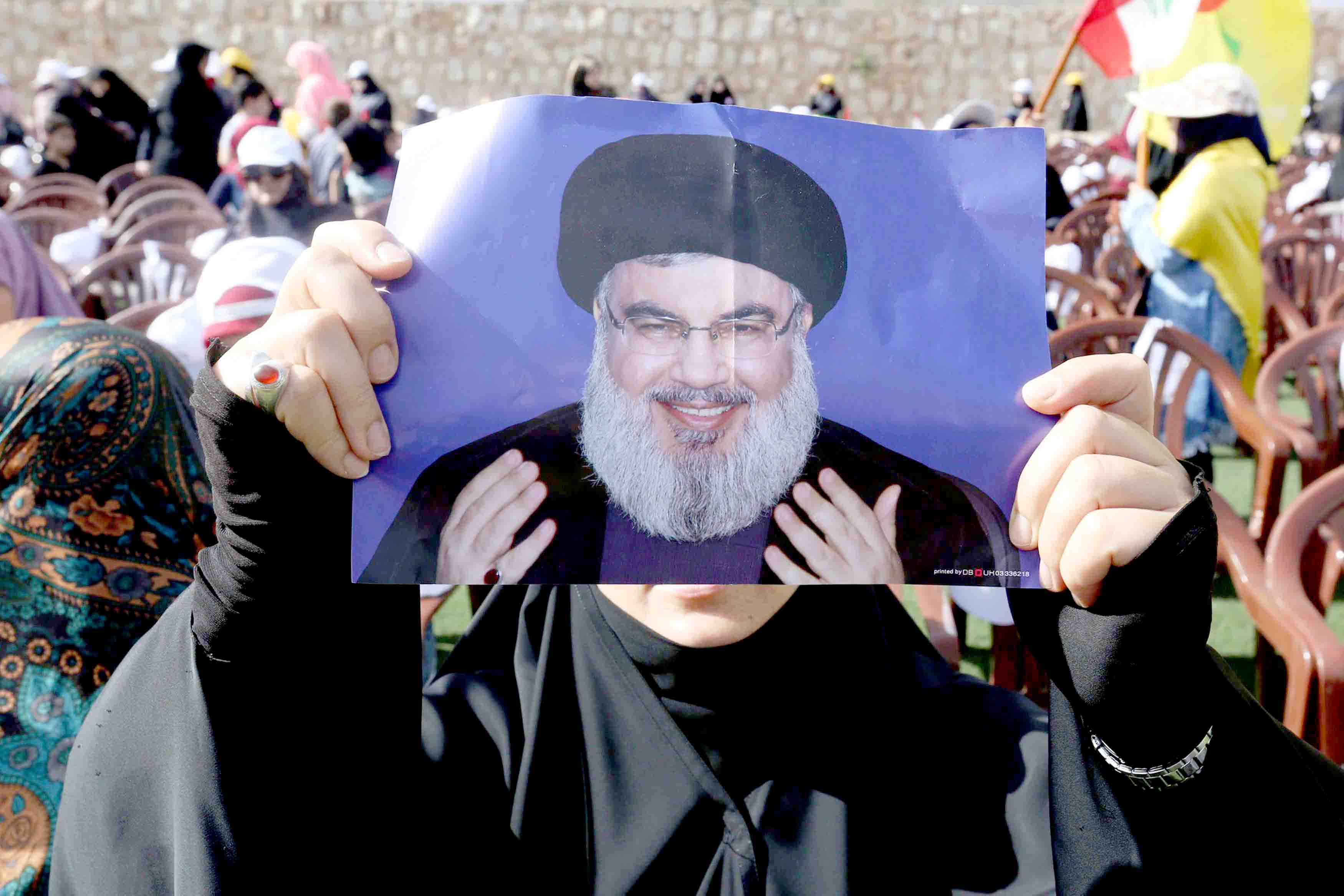 A Hezbollah supporter carries a poster of the group's leader Sayyed Hassan Nasrallah in Maroun al-Ras village in southern Lebanon. (Reuters)