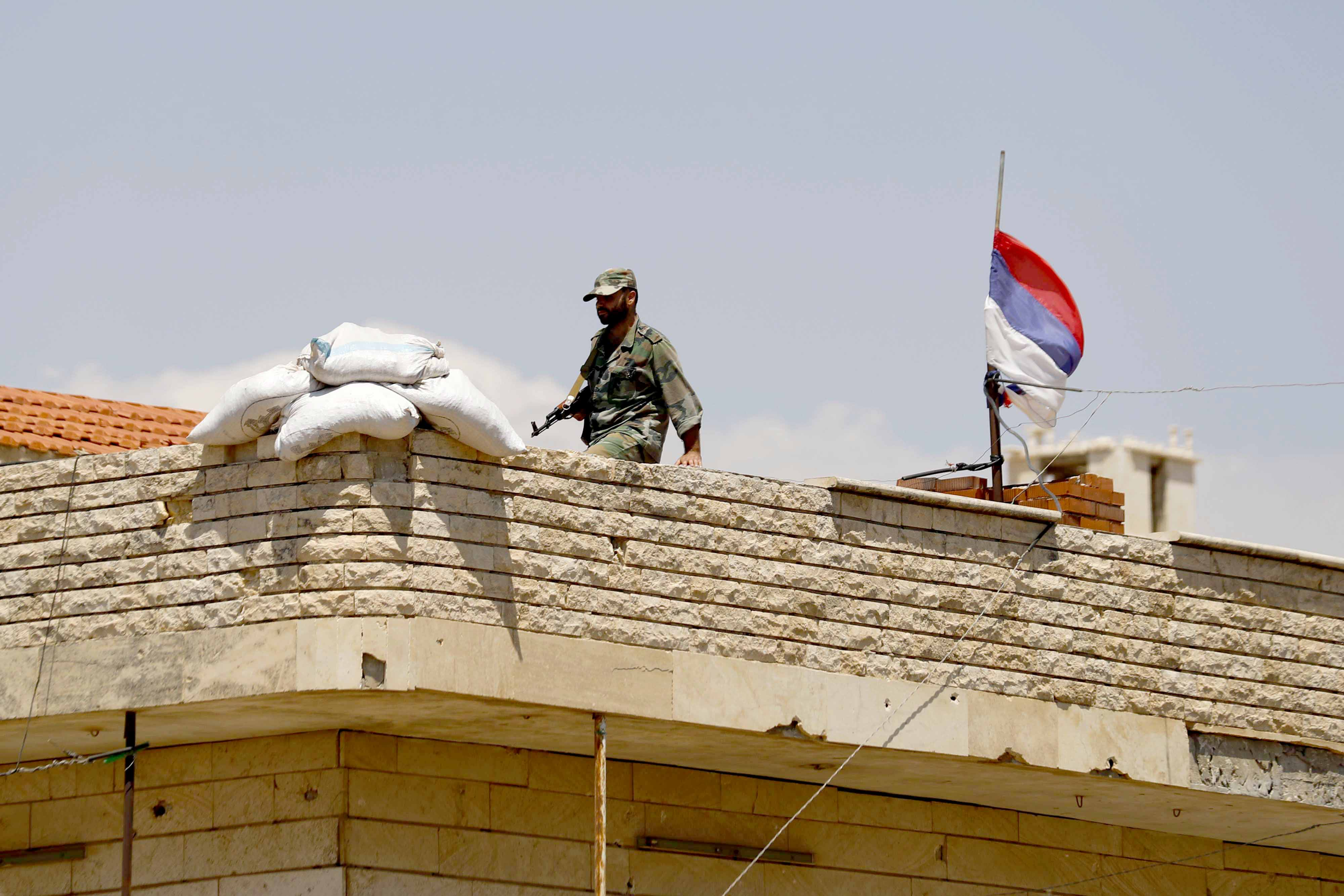 Up in the air. A Russian flag waves as a Syrian soldier walks on a roof of a military post overlooking the Damascus-Aleppo highway in Rastan. (AP)