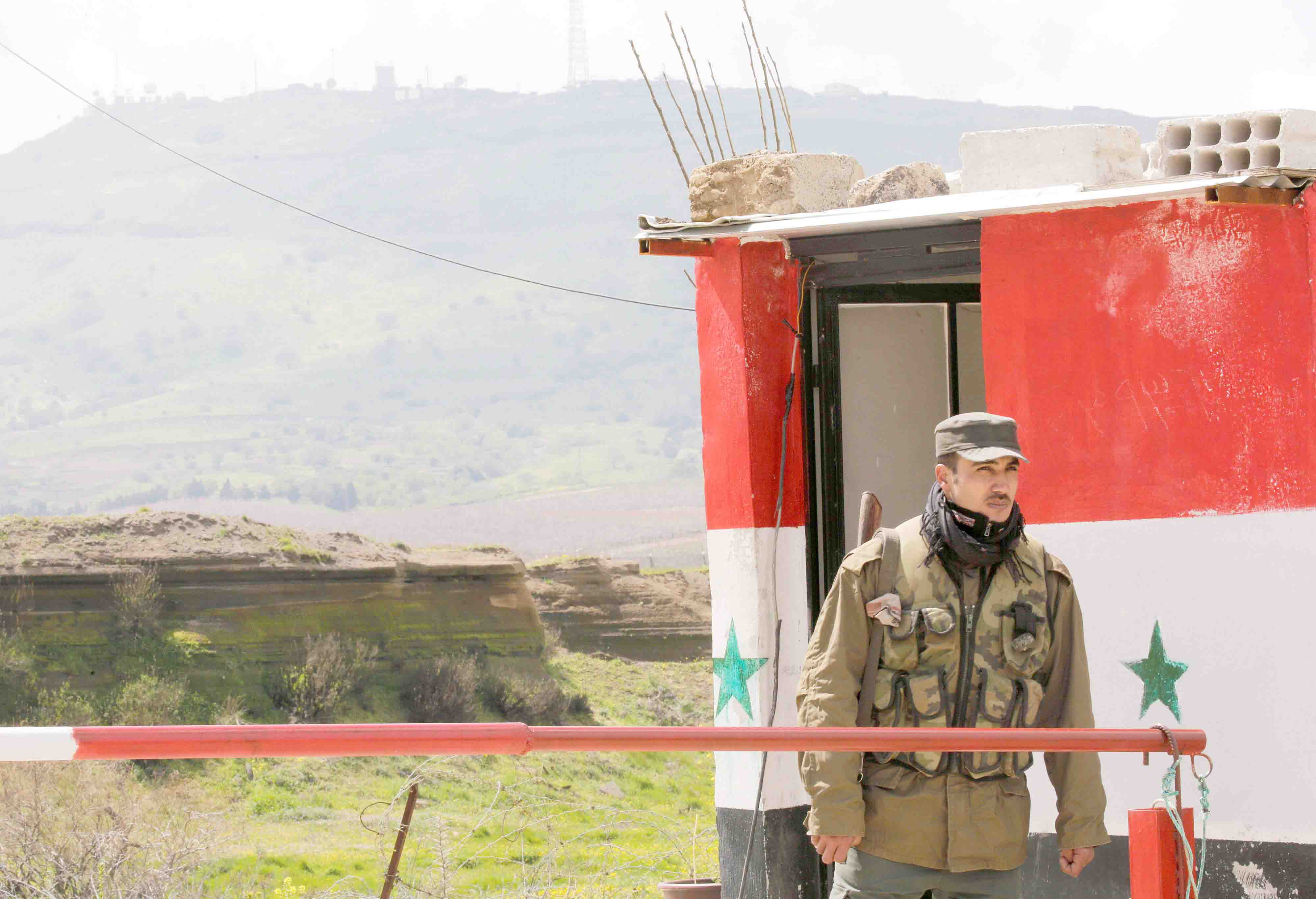 A Syrian Army soldier stands at a checkpoint at the Quneitra Crossing between the Israeli-controlled Golan Heights and Syria, March 26. (Reuters)