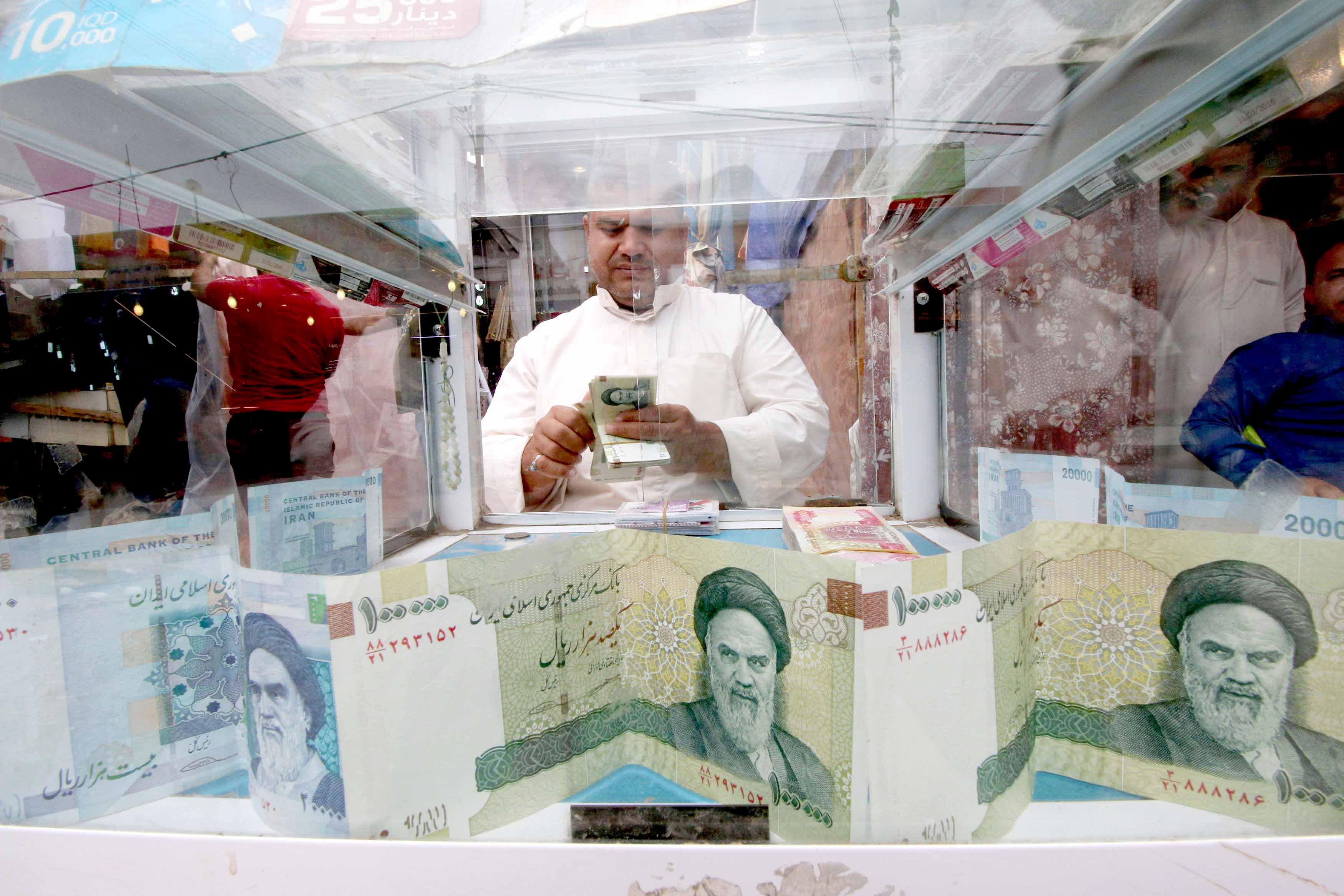 A man counts Iranian rials at a currency exchange shop in Basra. (Reuters)