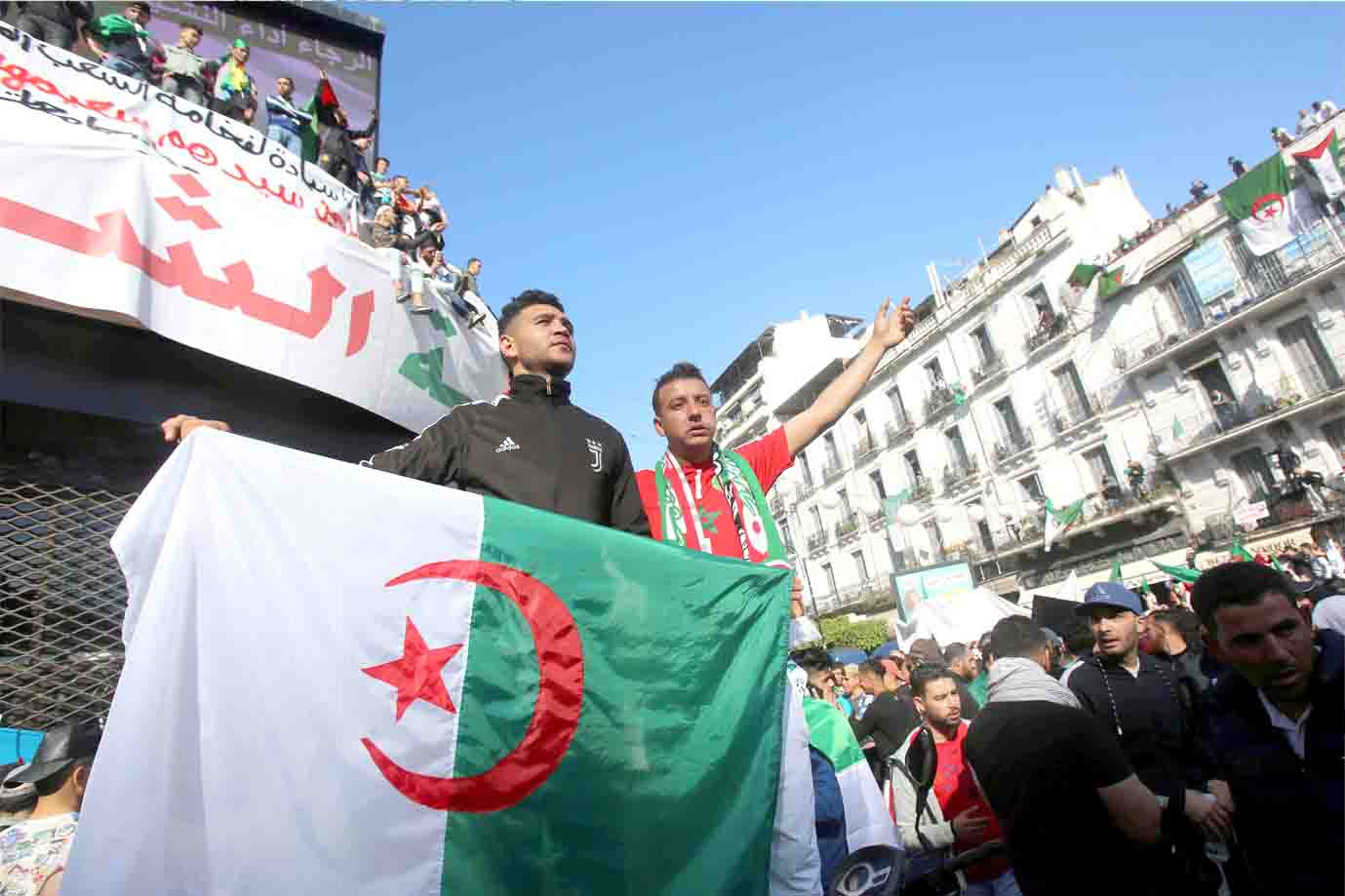 Men carry a national flag during a protest demanding radical change in Algiers, April 5. (Reuters)