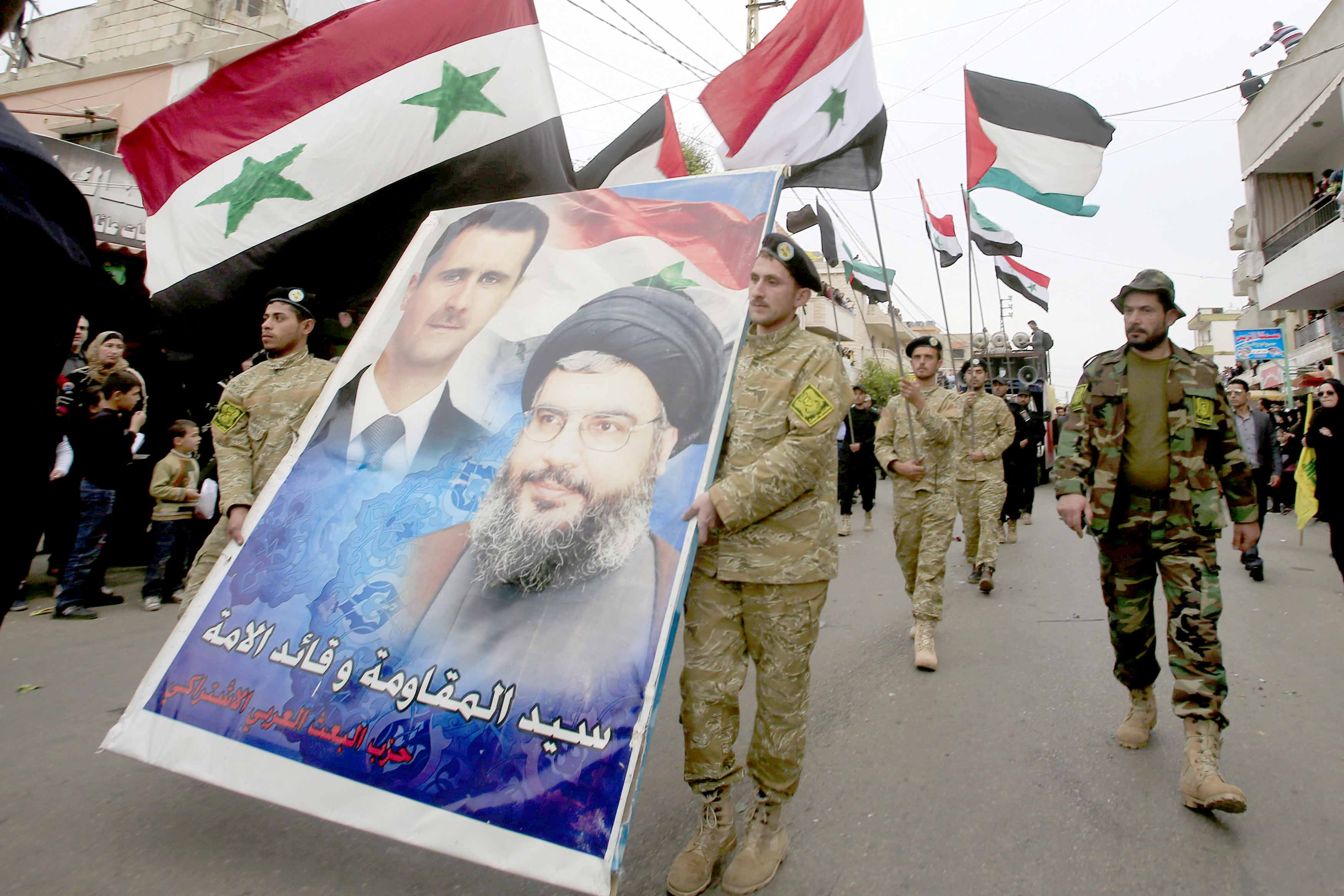 A strong comeback. Members of the Arab Socialist Ba'ath Party carry a poster of Syrian President  Bashar Assad and Hezbollah leader Sayyed Hassan Nasrallah in southern Lebanon.(Reuters)