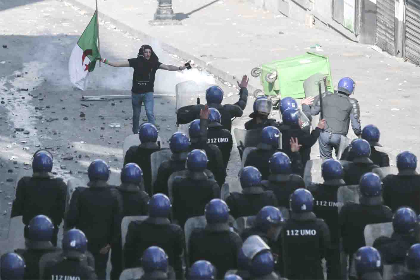Patience running thin. A protester gestures to police officers during clashes at a demonstration against the country's leadership in Algiers, April 12. (AP)