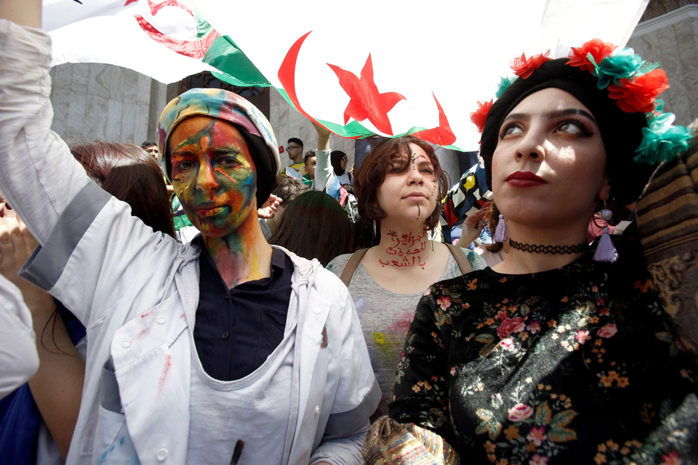 Algerian demonstrators with painted faces hold flags during antigovernment protests in Algiers, April 23. (Reuters)