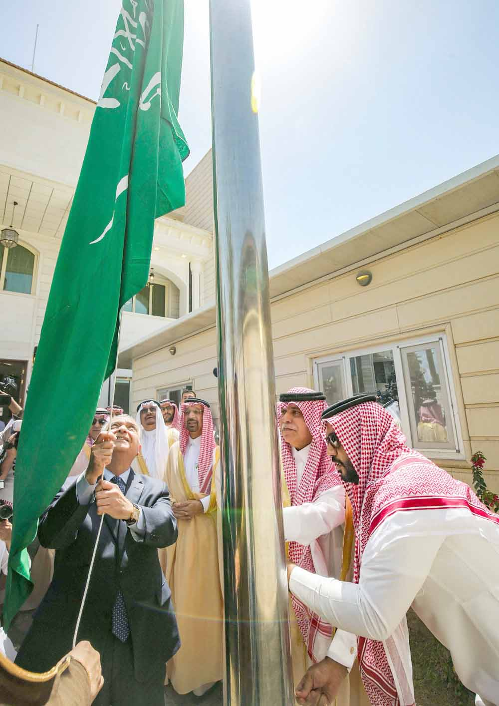 A new phase in relations. Iraqi Foreign Minister Mohammad Ali al-Hakim (C-L) raises the Saudi flag alongside Saudi Trade and Investment Minister Majid al-Qasabi (2nd-R) during the inauguration of the Saudi consulate compound in Baghdad, April 4. (AFP)