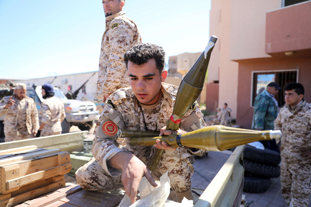 Members of Misrata forces, under the protection of Tripoli's forces, prepare themselves to go to the front line in Tripoli, Libya, April 8. (Reuters)