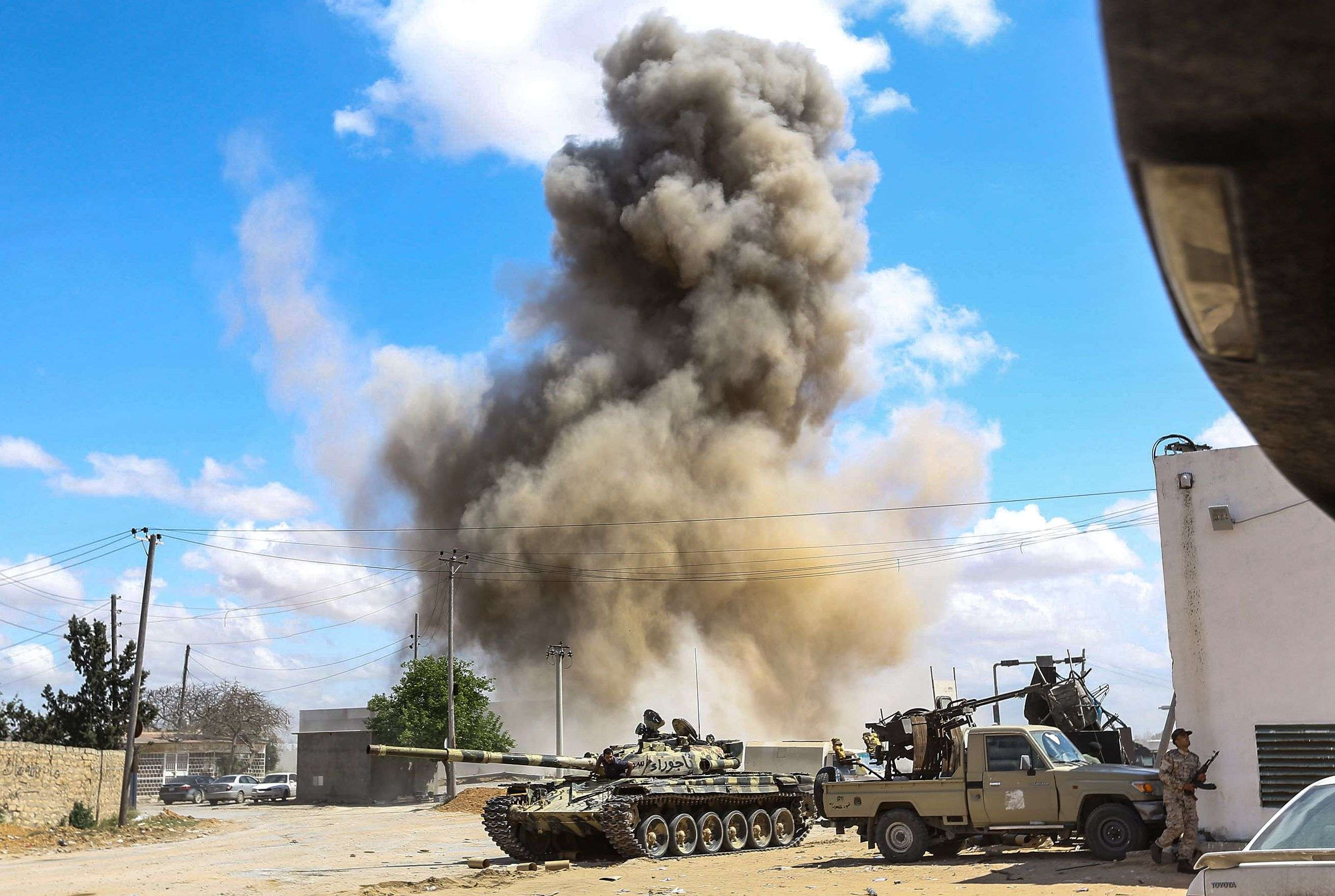 Military thrust. Smoke rises behind a tank and technicals belonging to forces loyal to Libya's  Government of National Accord during clashes in the suburb of Wadi Rabie, south of Tripoli. (AFP)