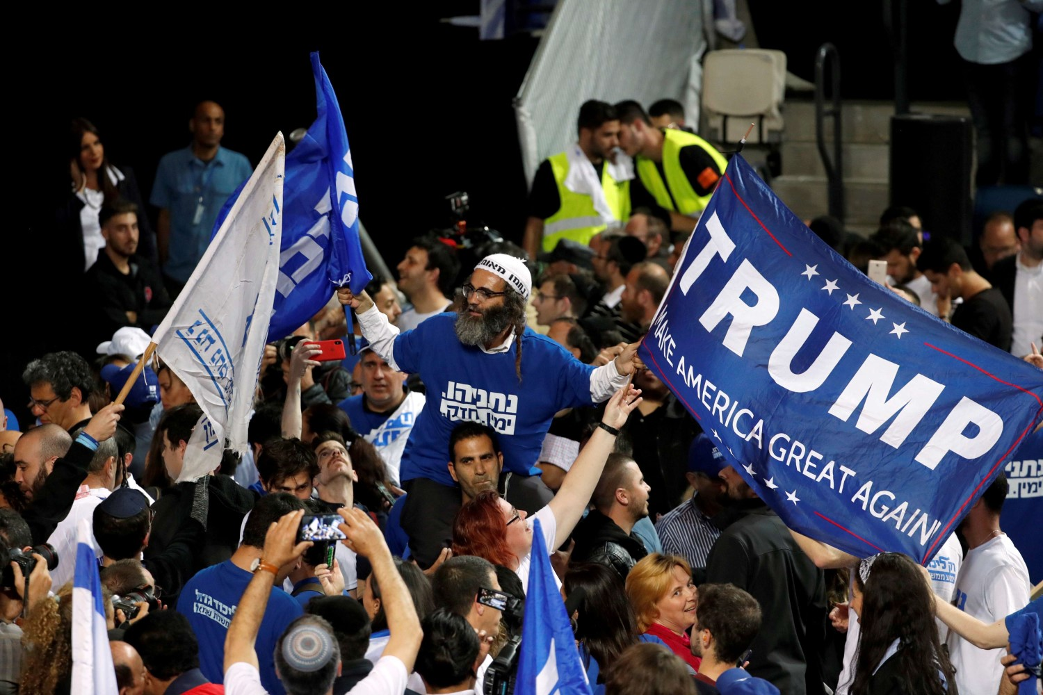 A supporter of Israeli Prime Minister Benjamin Netanyahu's Likud party waves flags as the crowd reacts to exit polls in Israel's parliamentary election at the party headquarters in Tel Aviv, Israel April 10, 2019. (Reuters)