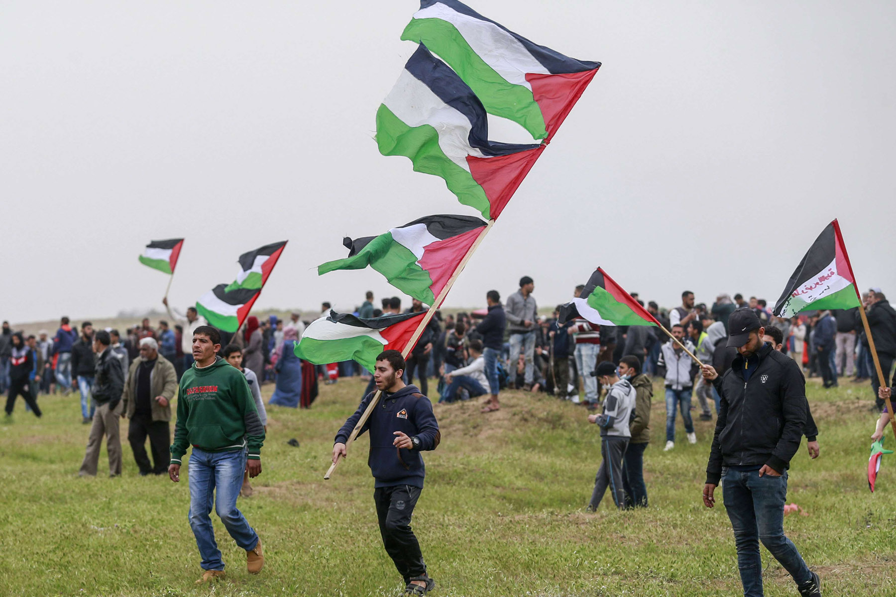 Palestinian protesters wave national flags during a demonstration near the border with Israel, east of Gaza City, March 30. (AFP)