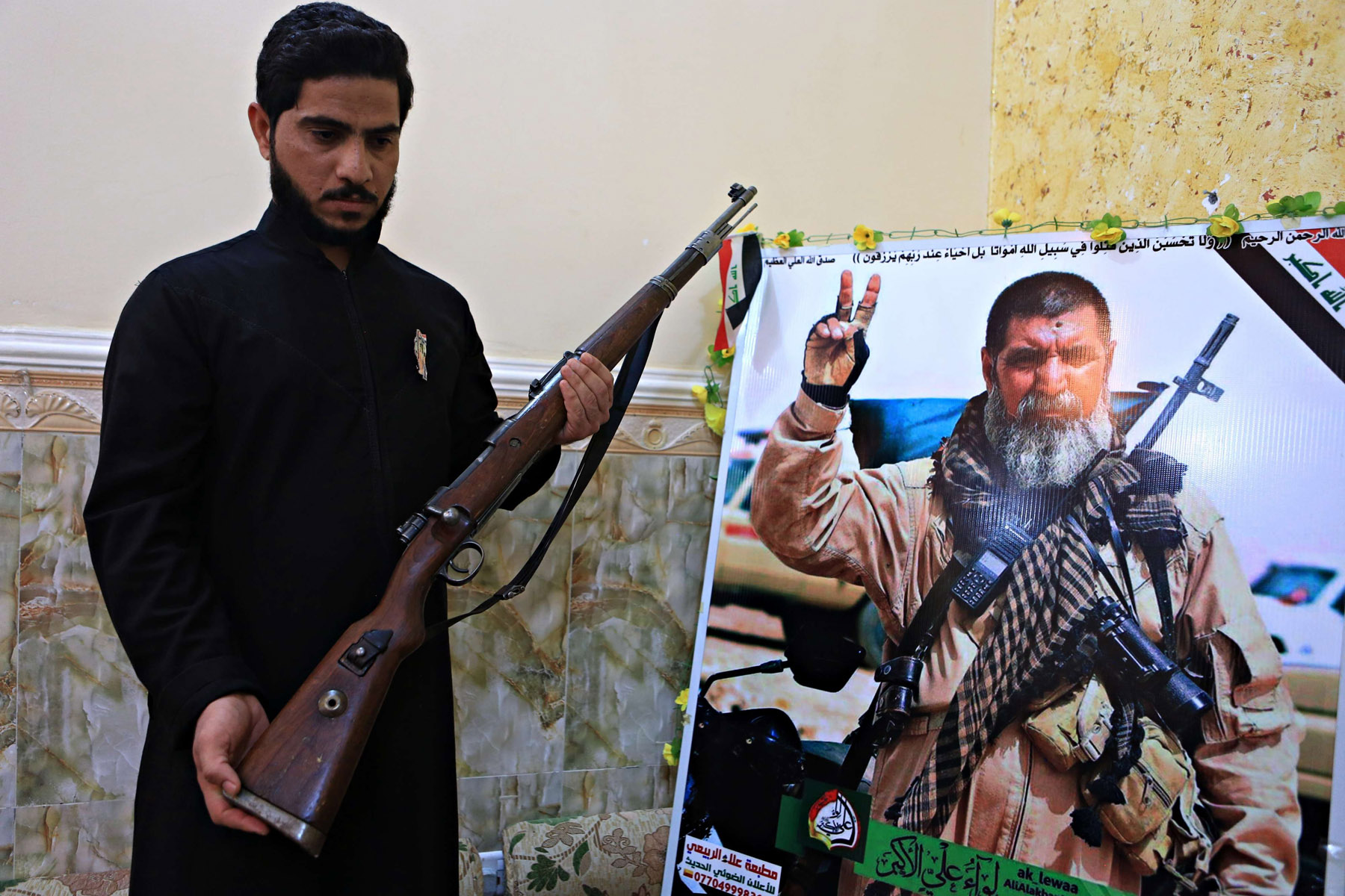 A militiaman with Popular Mobilisation Forces poses with a weapon next to his father's poster in his home in Basra. (AP)