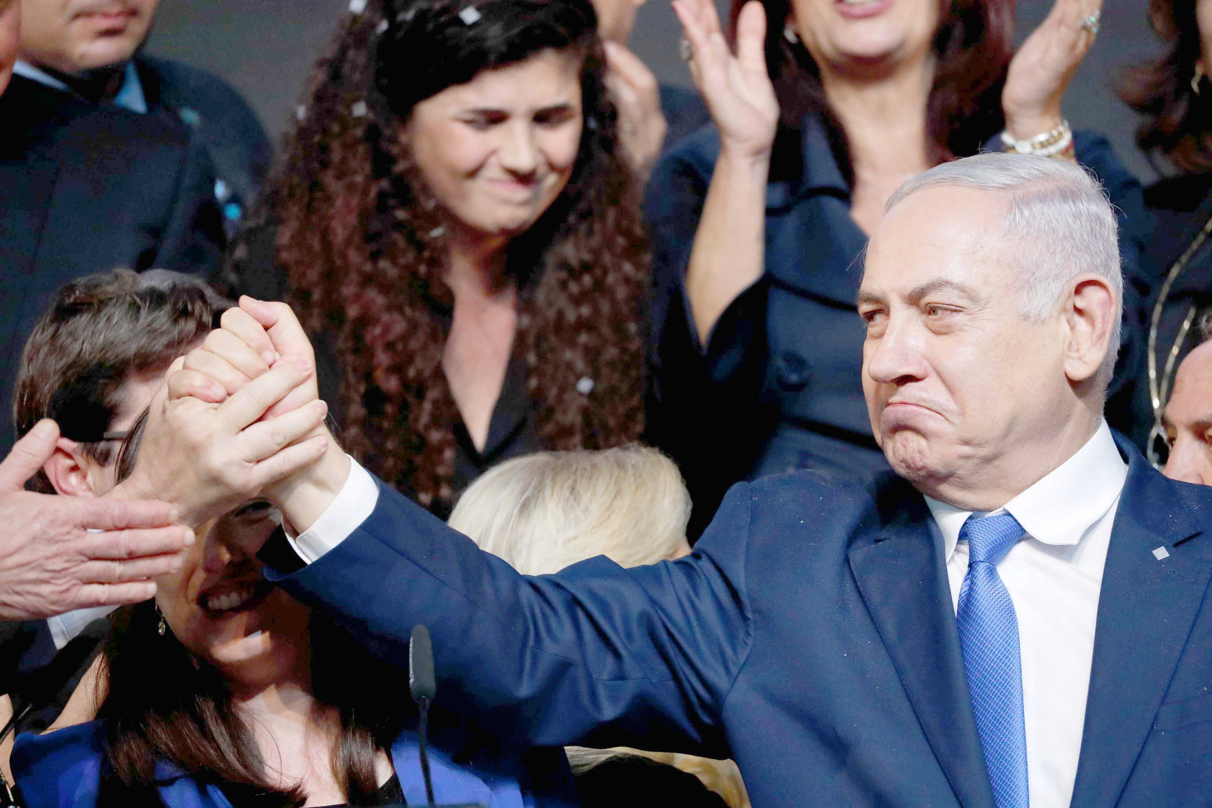 Israeli Prime Minister Binyamin Netanyahu shakes hands with a supporter at Likud party headquarters in Tel Aviv, April 10. (AFP)