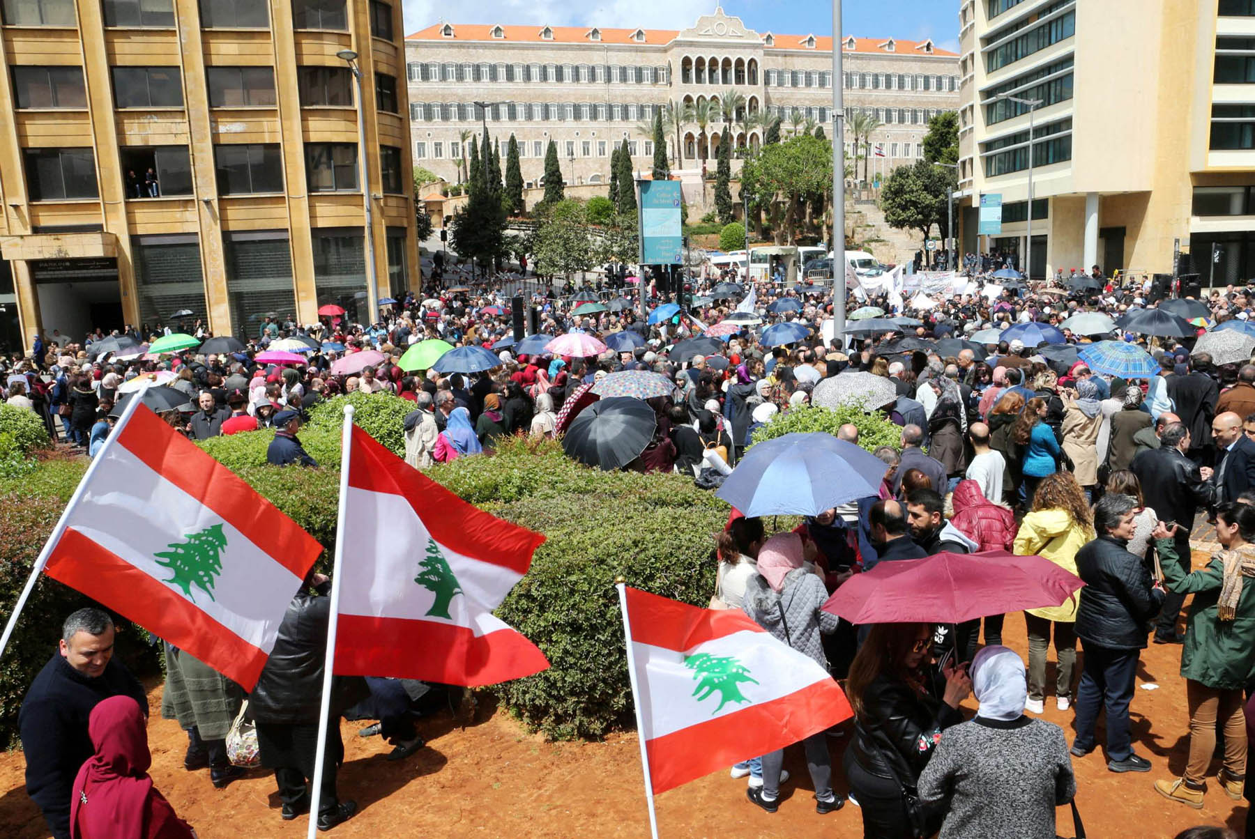 Brewing storm. Public sector workers hold Lebanese flags during a protest against cuts to their salaries in downtown Beirut, April 17. (Reuters)