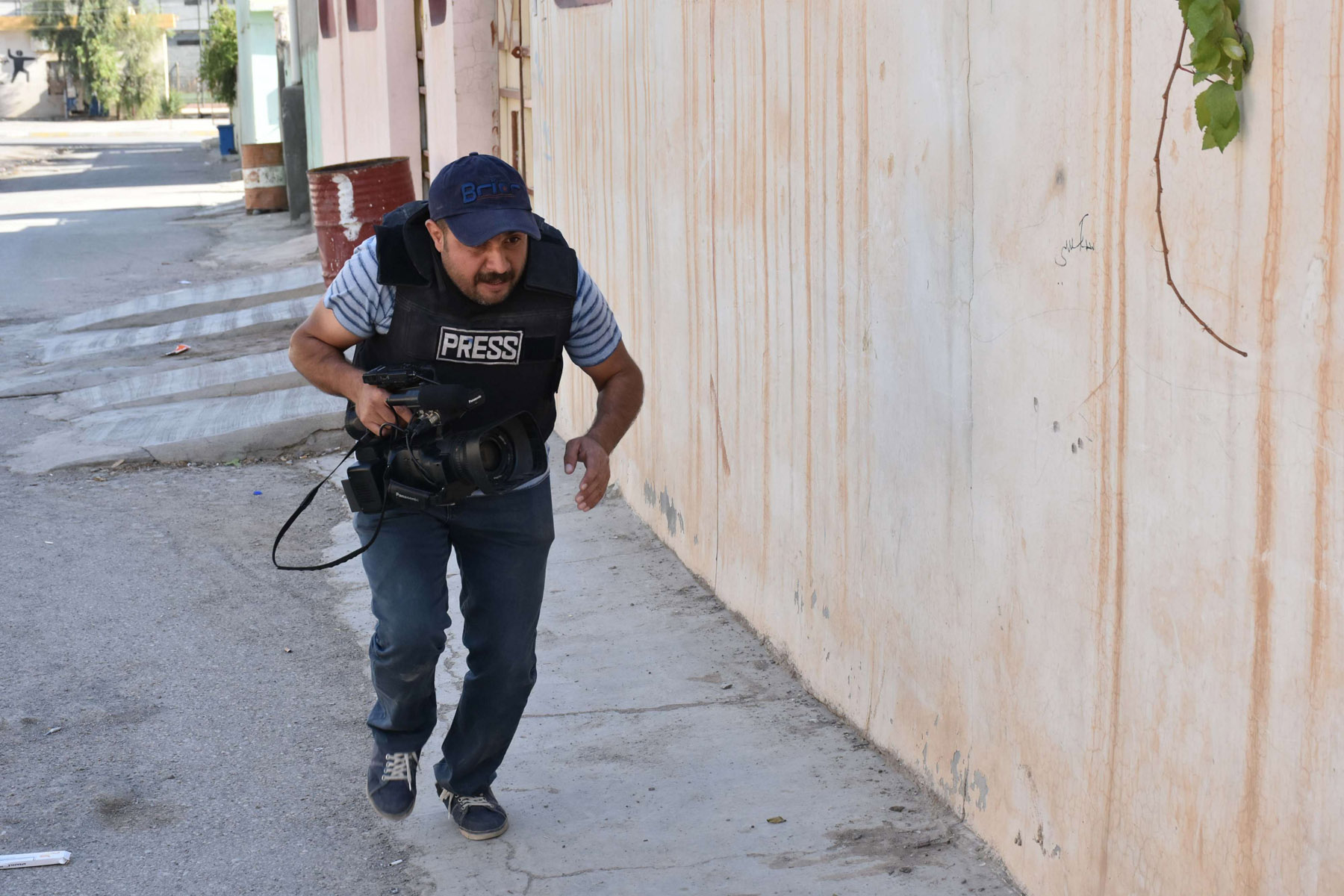 A 2017 file picture shows a video journalist running for cover behind a wall amid fighting in the region of Altun Kupri, about 50km from Erbil. (AFP)