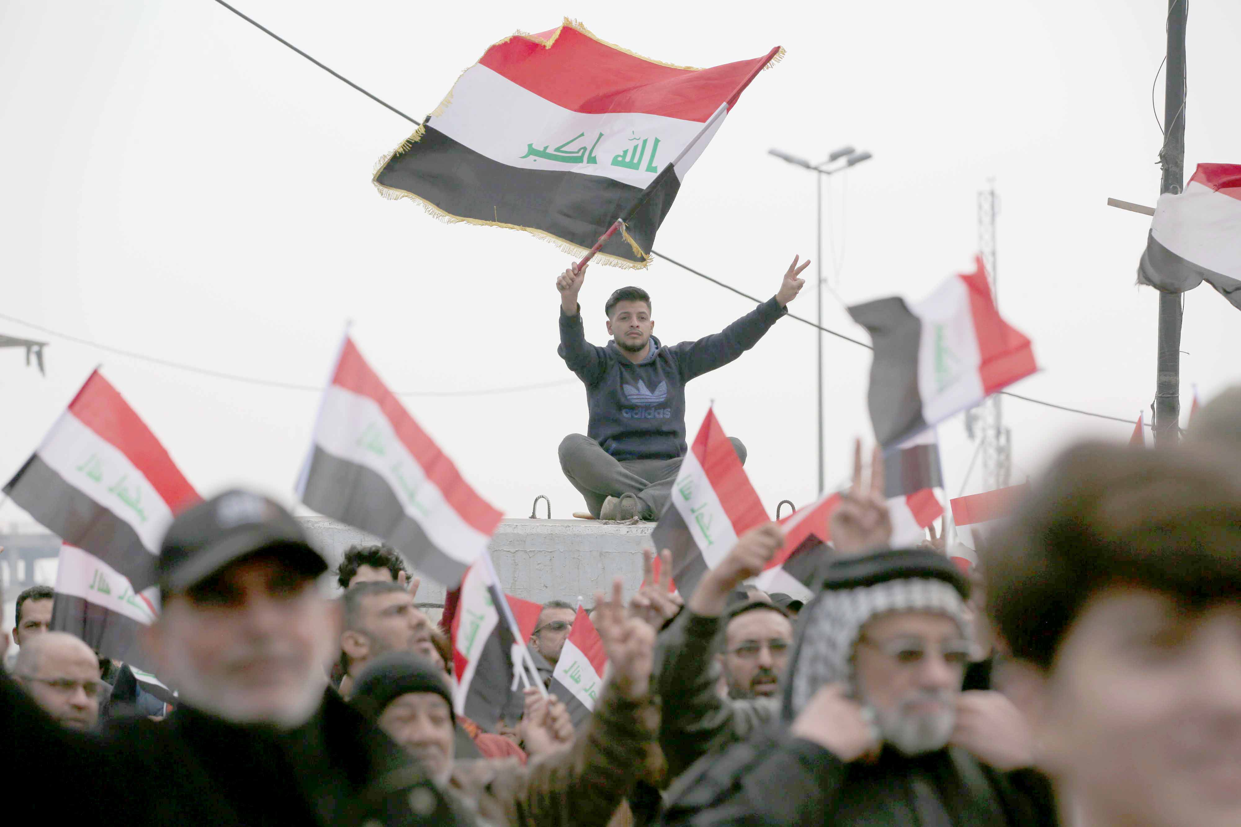 Stirring unrest. Iraqis hold flags during a protest against corruption at Tahrir Square, last February.(DPA)