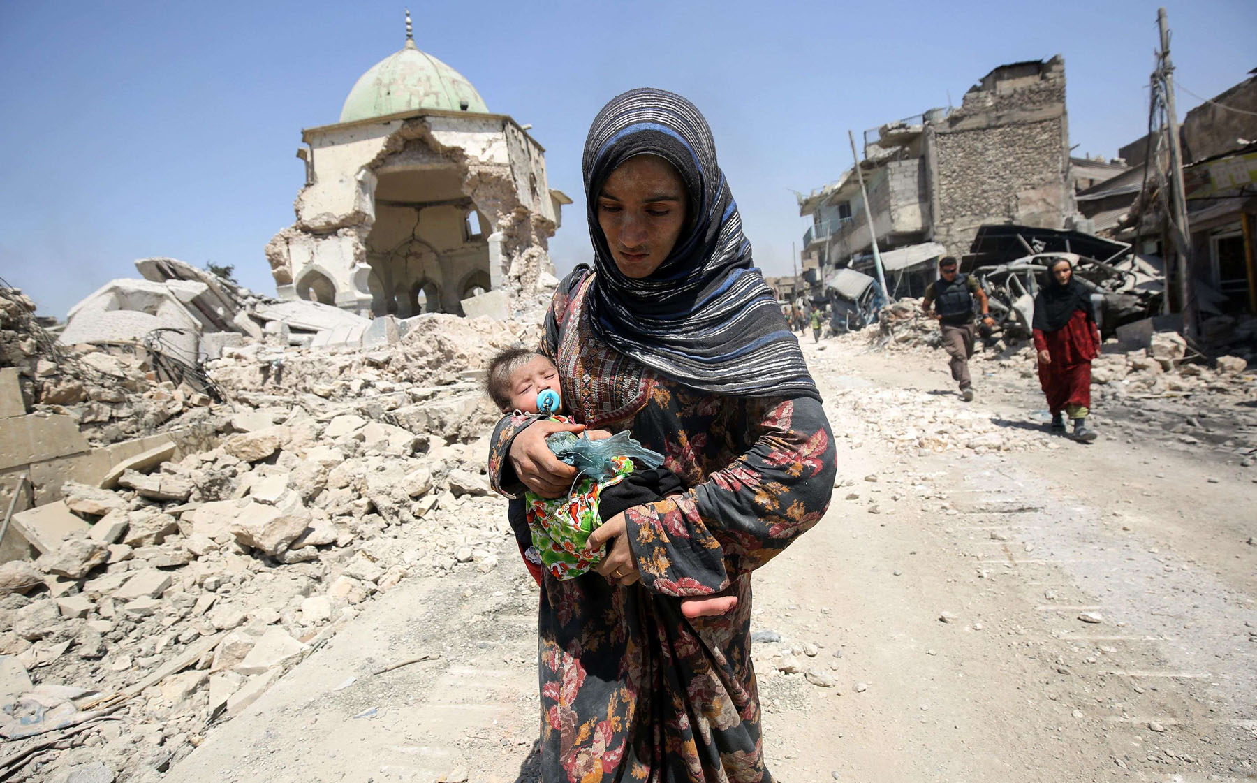 Traumatic memories. A 2017 file picture shows an Iraqi woman and her child walking by the destroyed al-Nuri mosque while fleeing from the Old City of Mosul. (AFP)