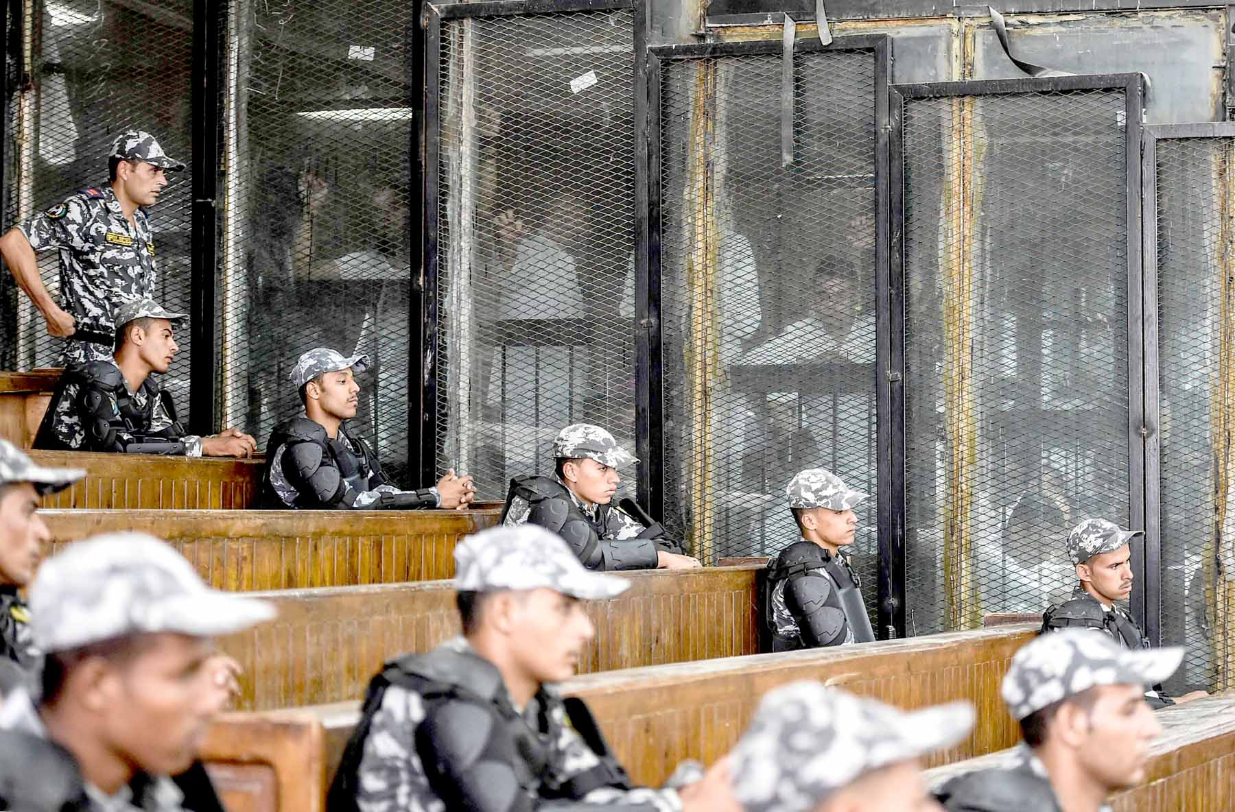 Maintained pressure. Members of Egypt's banned Muslim Brotherhood are seen inside a glass dock during their trial in Cairo, last July. (AFP)