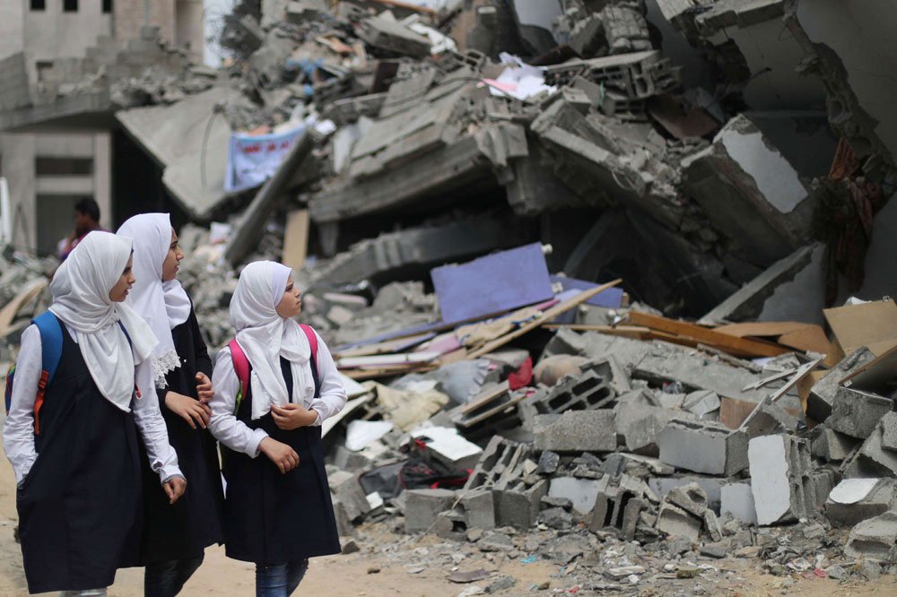 Palestinian students look at a building that was destroyed by Israeli air strikes near their damaged school in Gaza, May 7. (Reuters)