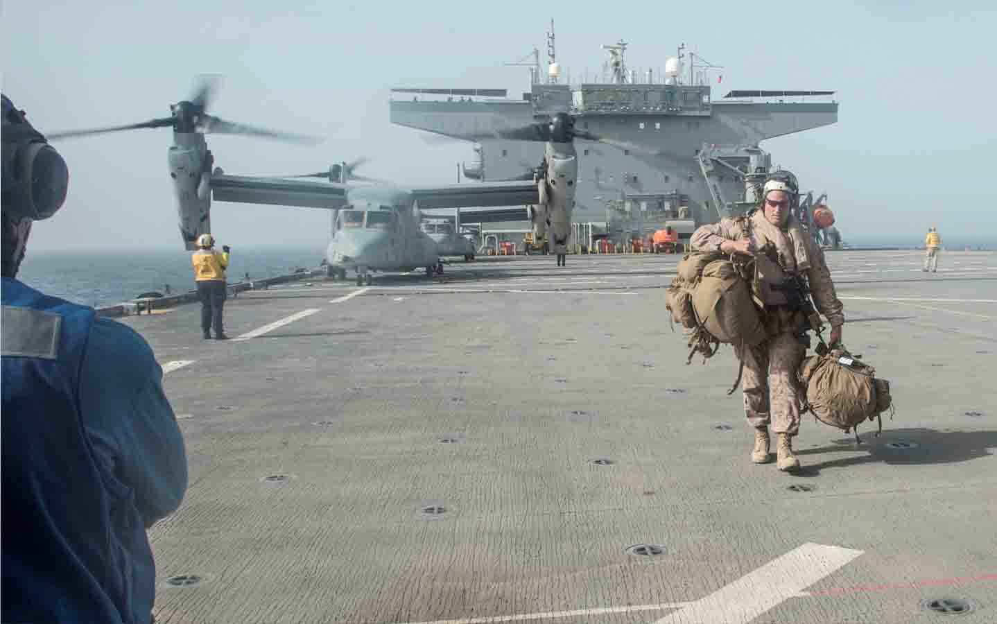 Security concerns. A US Marine Corps officer carries his gear across the flight deck of the USS Lewis B. Puller upon embarkation in the Arabian Gulf, May 11. (Reuters)
