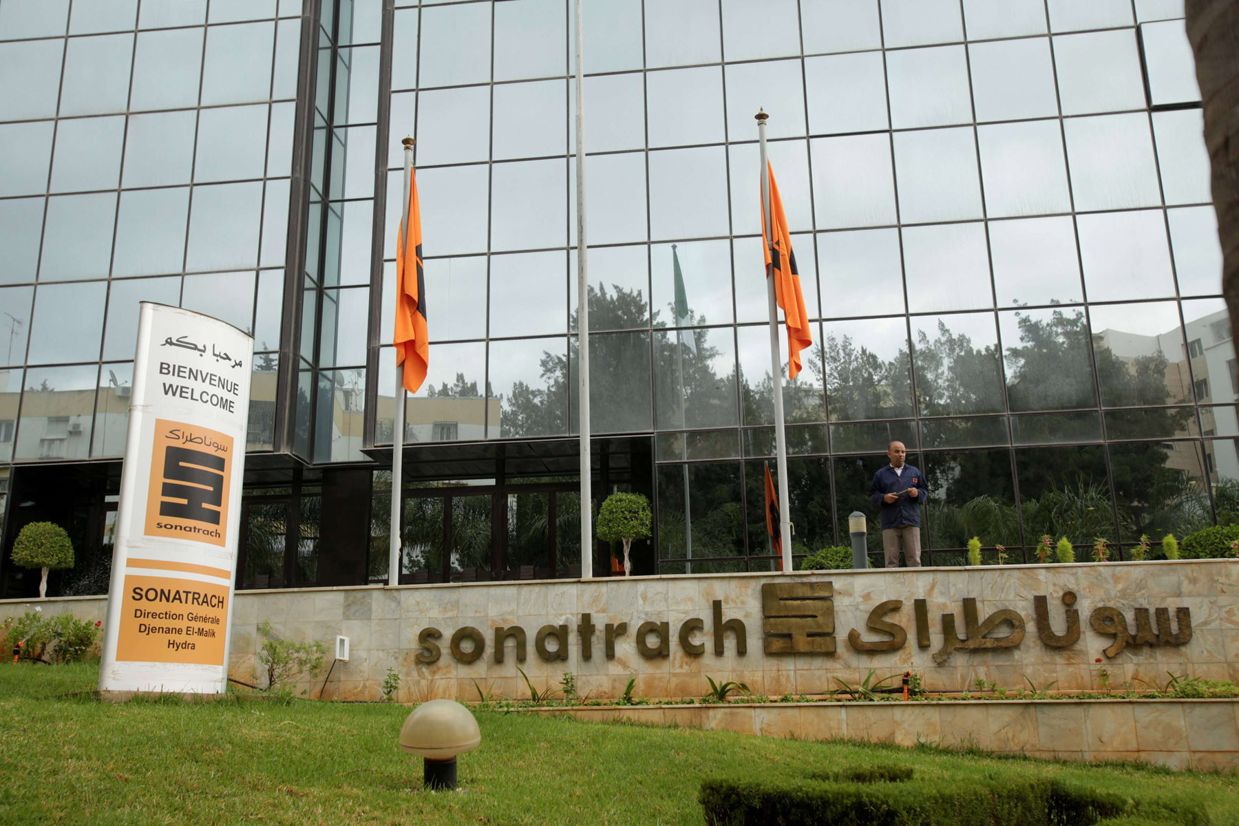 An employee stands near the headquarters of the state energy company Sonatrach in Algiers. (Reuters)