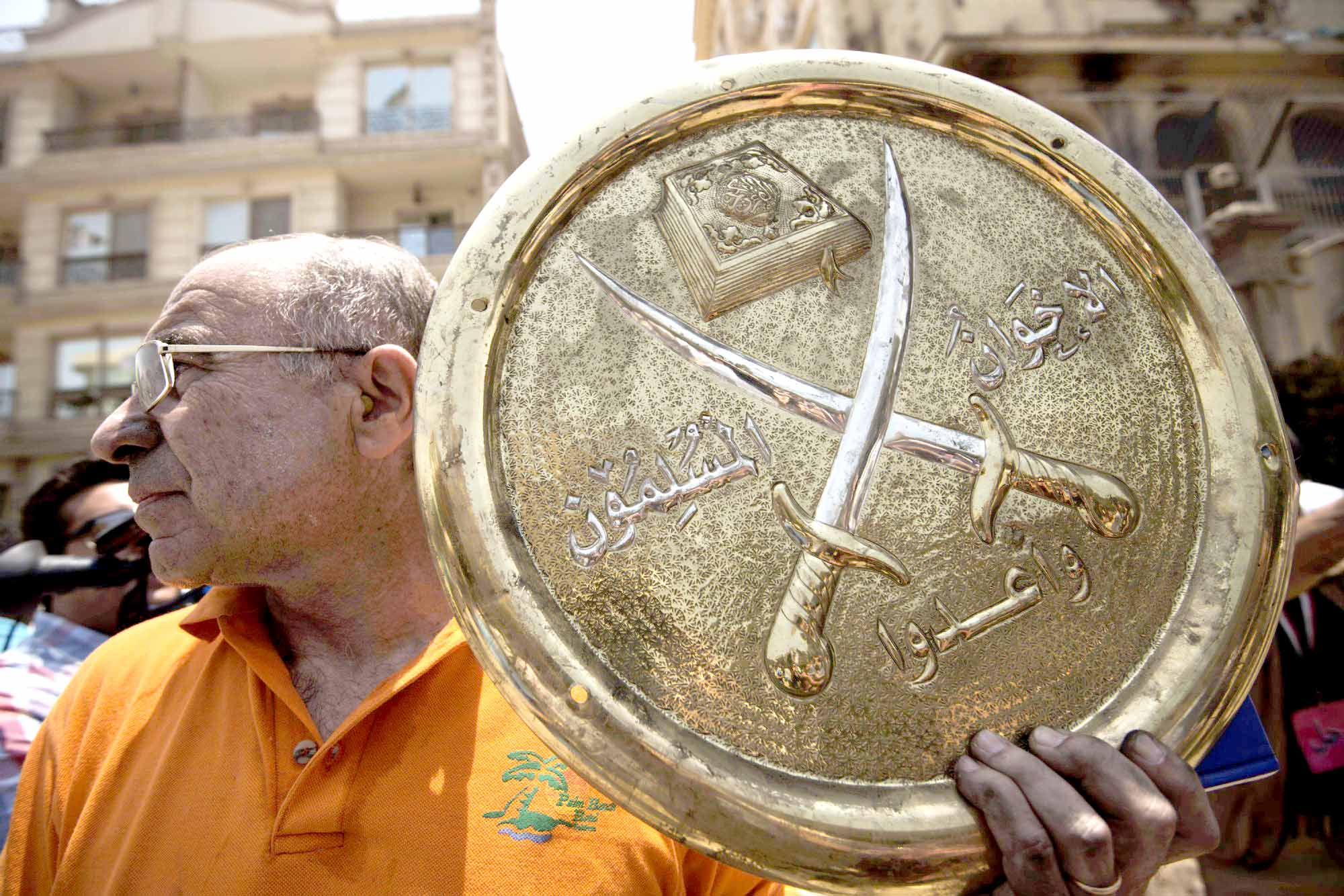 Challenging the swords.  A 2013 file picture shows a man holding a plaque of the Muslim Brotherhood emblem that was removed from the party's burned-out headquarters in the Moqattam district of Cairo.  (AFP)