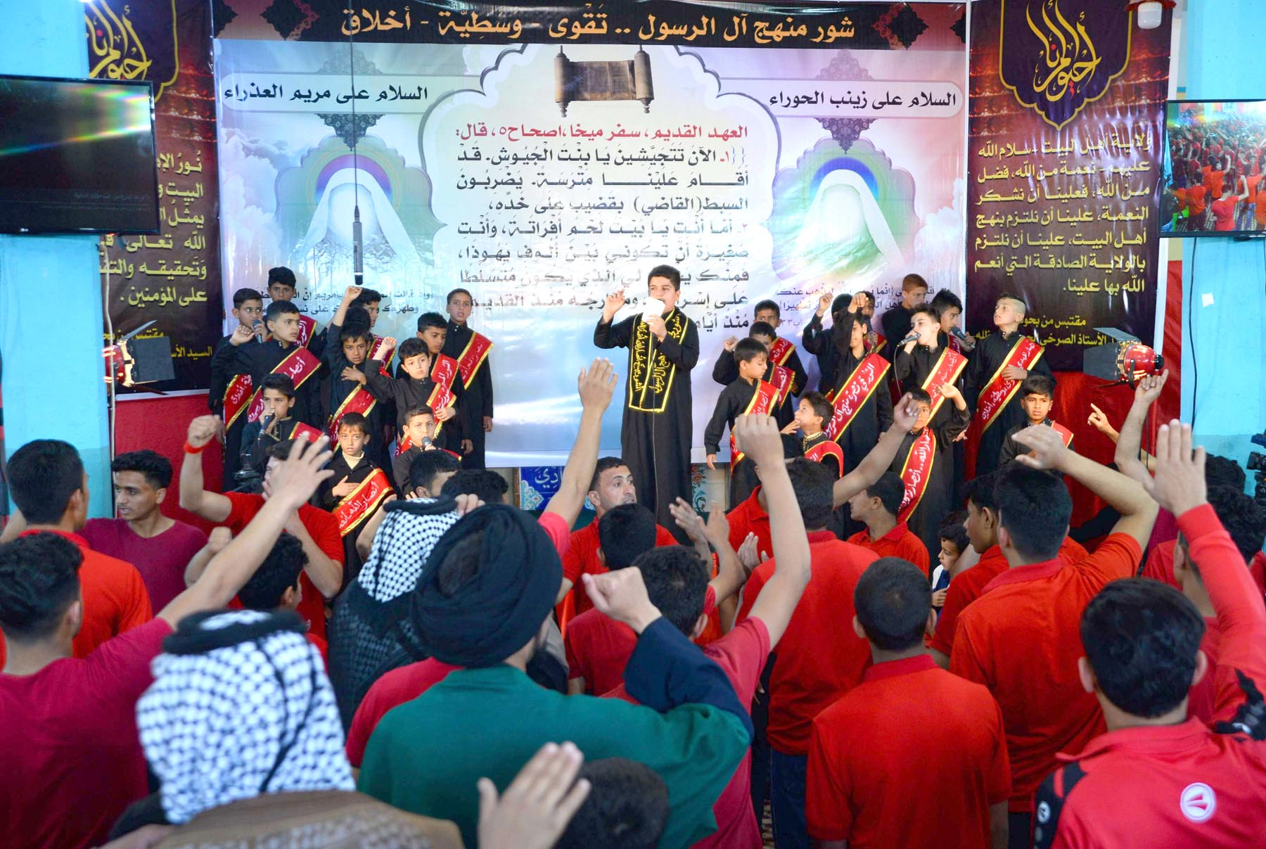 A young performer in a black robe chants as  Iraqi Shia youth take part in a mourning ceremony at their local mosque in the town of Midhatiya, south of Baghdad. (AFP)