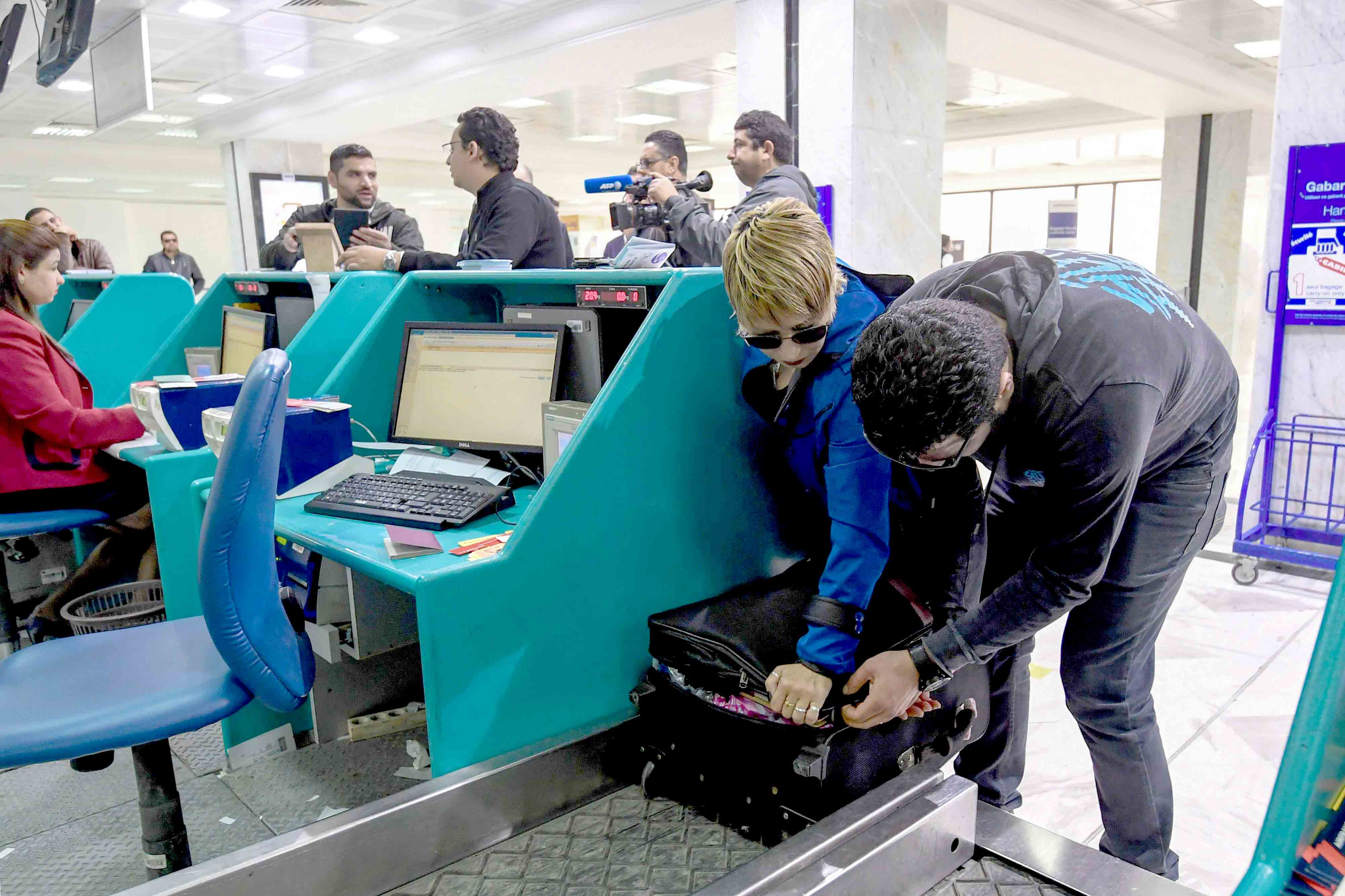 Still a way to go. A Tunisian couple bound for London pack away  their electronics in their luggage as they check-in for a flight at the Tunis-Carthage International Airport, March 25, 2017.(AFP)