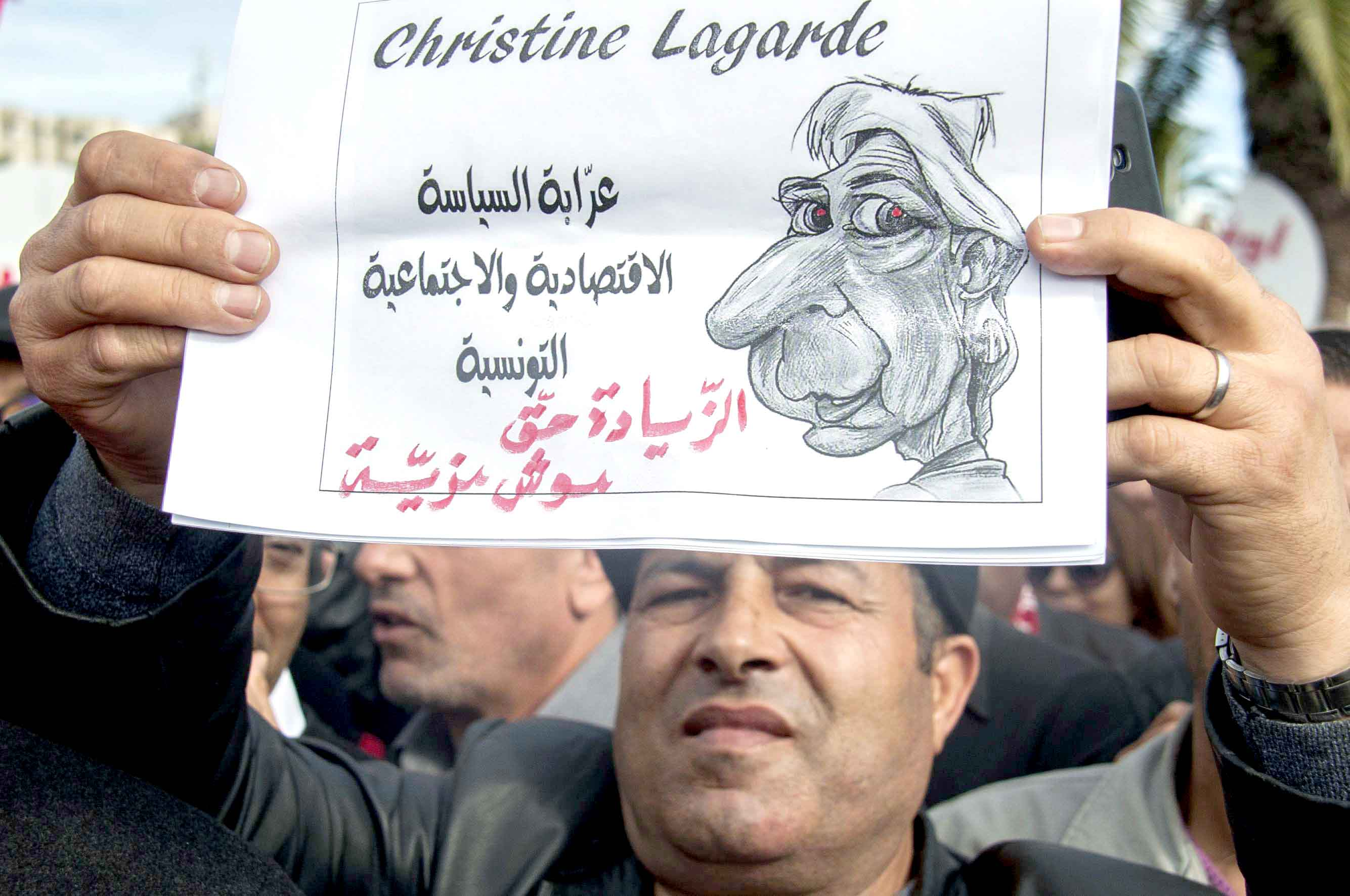 A Tunisian public sector worker holds a poster criticising IMF Managing Director Christine Lagarde in Tunis, last November.(AP)