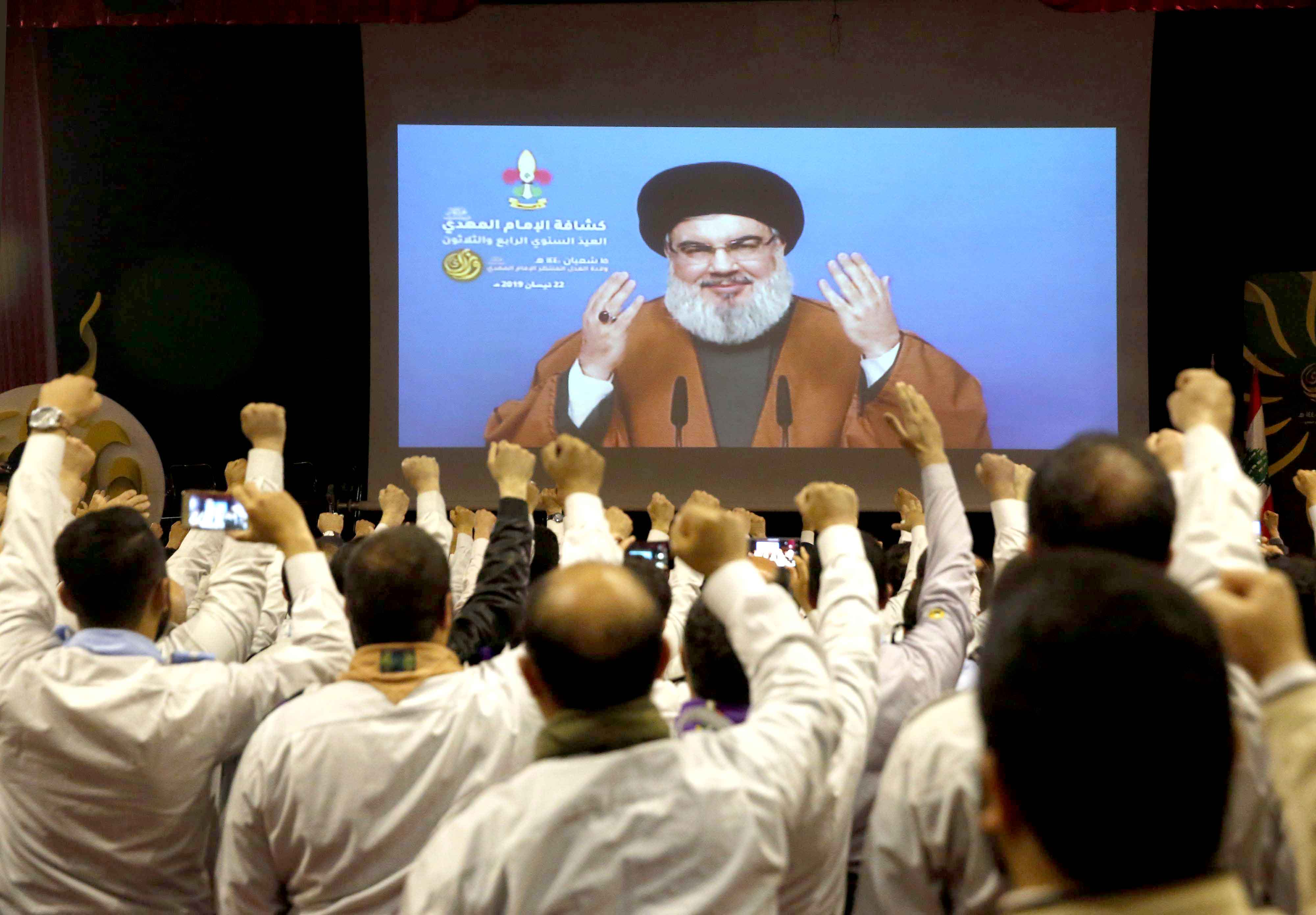Increasingly confident. Hezbollah scouts raise their fists as they listen to a speech of Hezbollah leader Sayyed Hassan Nasrallah, via a video link, in southern Beirut, April 22. (AP)
