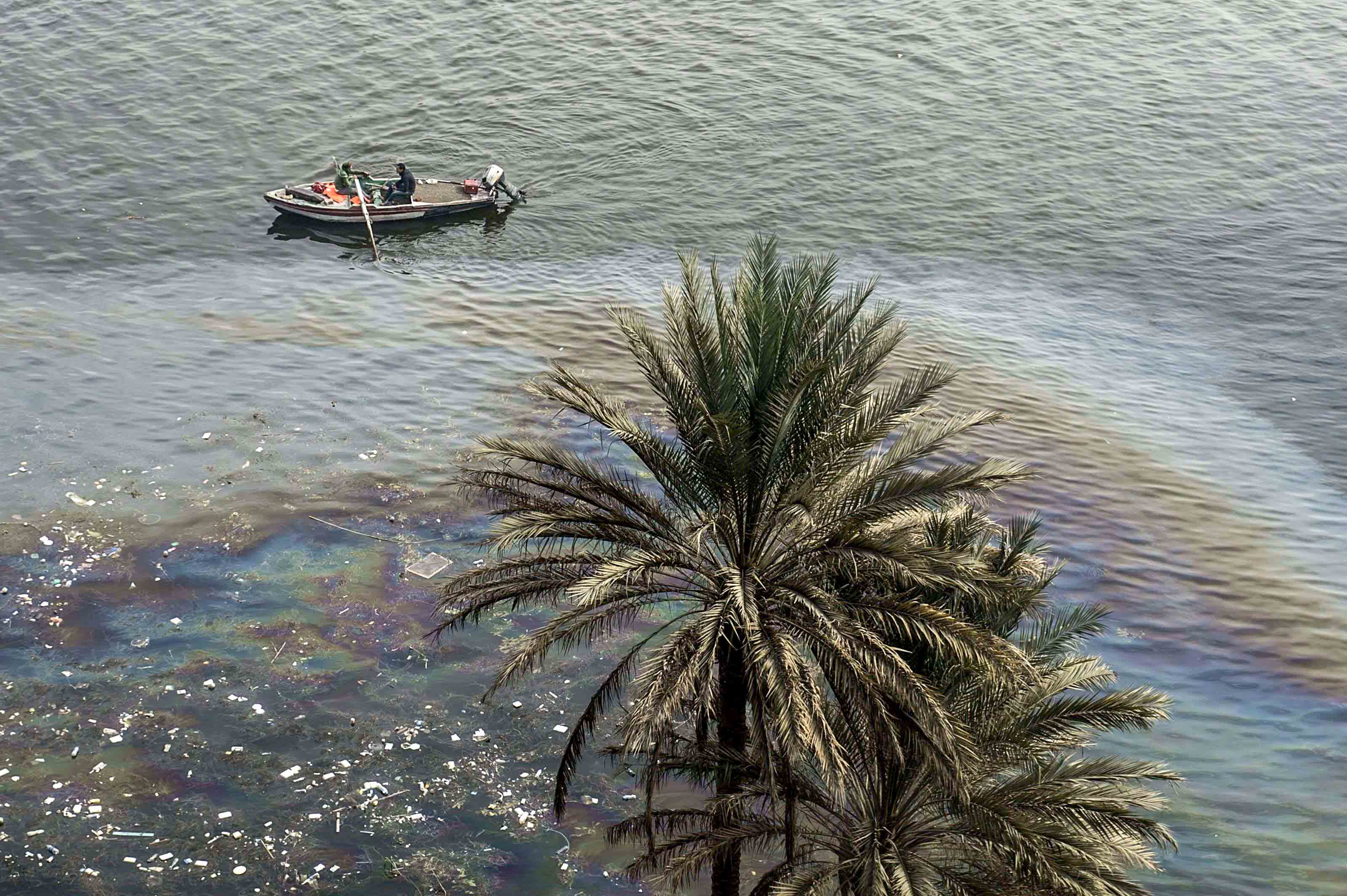 People ride a small boat past an oil spill in the Nile River in Cairo. (AFP)