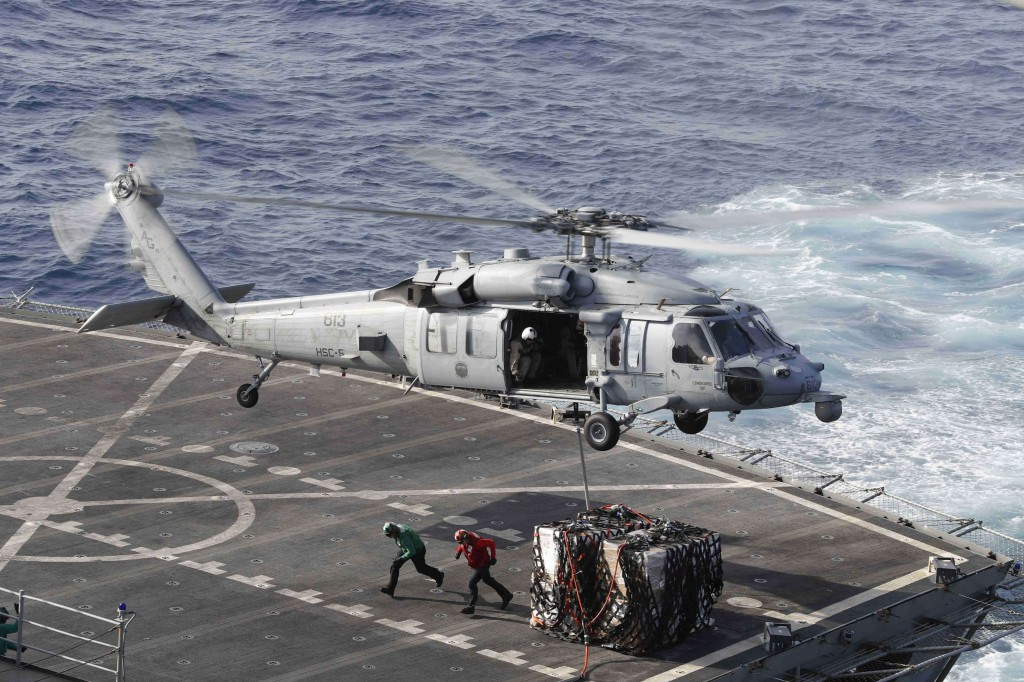 A MH-60S Sea Hawk helicopter transports cargo from the fast combat support ship USNS Arctic (T-AOE 8) to the Nimitz-class aircraft carrier USS Abraham Lincoln (CVN 72) during a replenishment-at-sea, May 19. (AFP)
