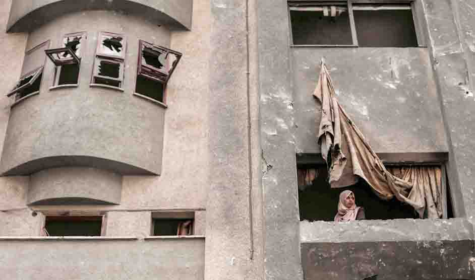 Grudges old and new. A Palestinian woman looks out of the window of a building, damaged by an Israeli air strike, last November. (AFP)