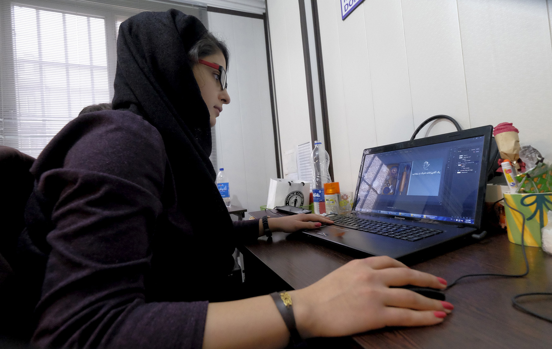An Iranian woman works on her laptop in Tehran. (Reuters)