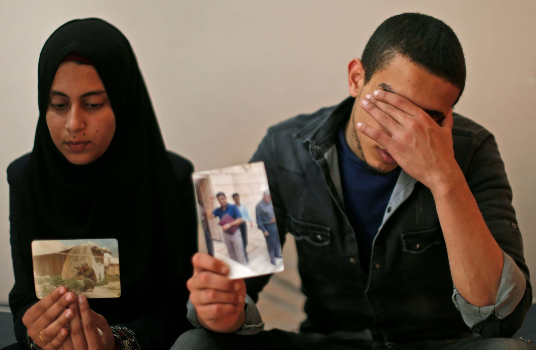 The daughter (L) and son of Zaki Mubarak hold his pictures during an interview in central Gaza Strip, last April. (AFP)