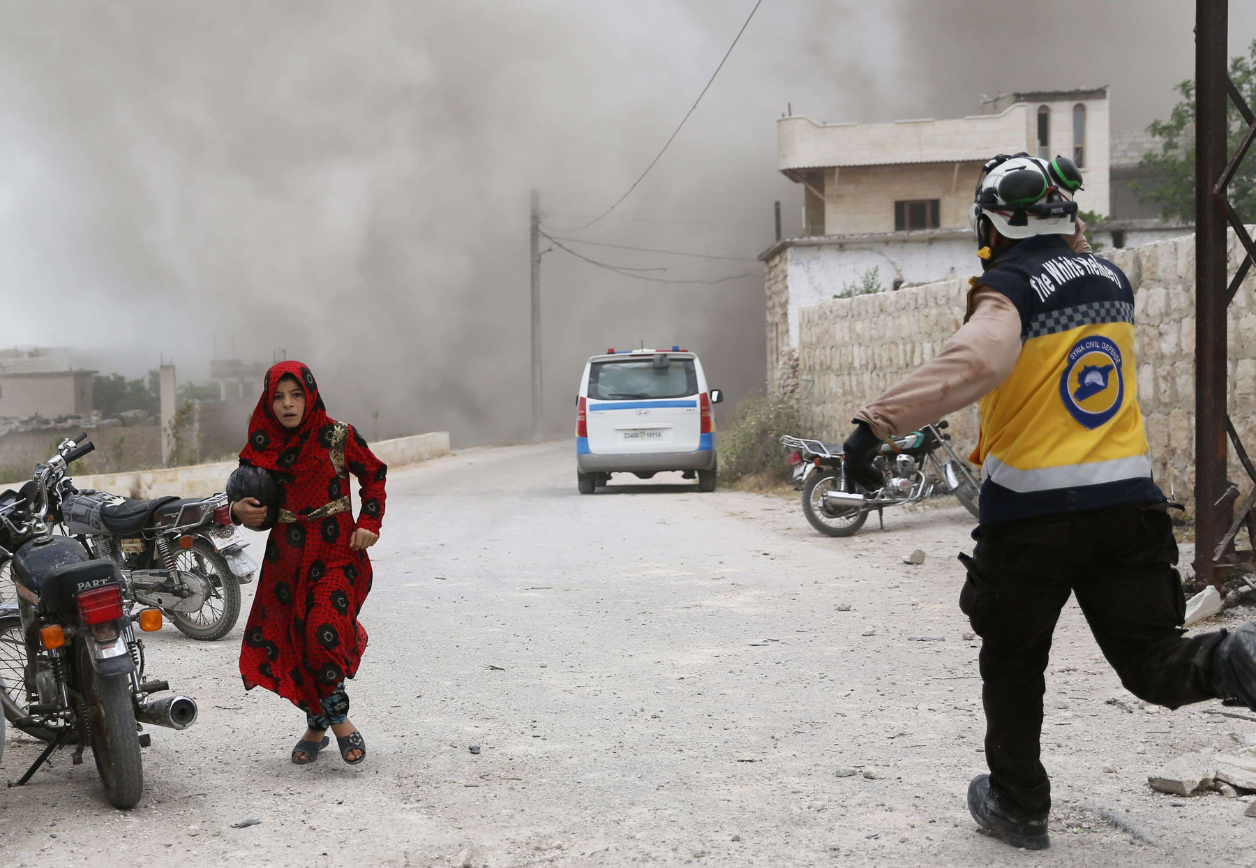 A Syrian civil defence rescuer runs past a girl trying to take cover during an air strike by pro-regime forces on the market town of Kfar Ruma in Syria's Idlib province, May 30. (AFP)