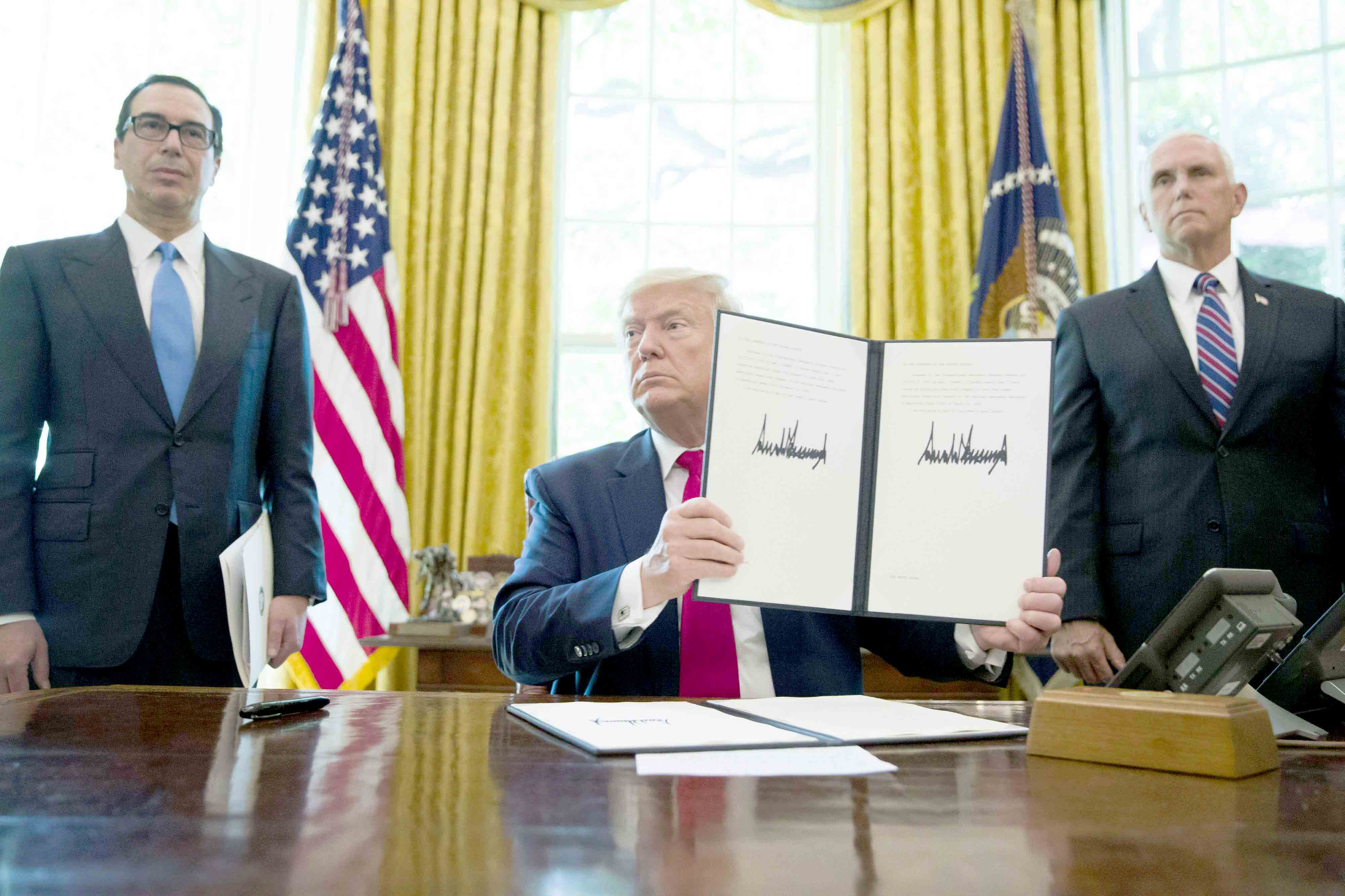 Escalatory moves. US President Donald Trump holds up a signed executive order to increase sanctions on Iran, accompanied by Treasury Secretary Steve Mnuchin, left, and Vice President Mike Pence, at the White House, in Washington, June 24.(AP)