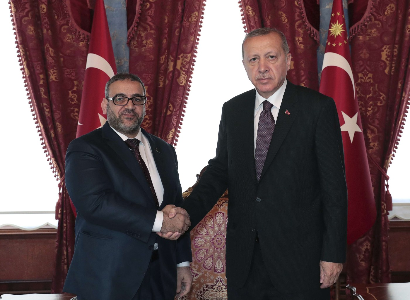 Turkish President Recep Tayyip Erdogan, right, and Khaled Al-Meshri, President of the High Council of State of Libya, shake hands before a meeting, in Istanbul, Friday, April 19, 2019. (AP)