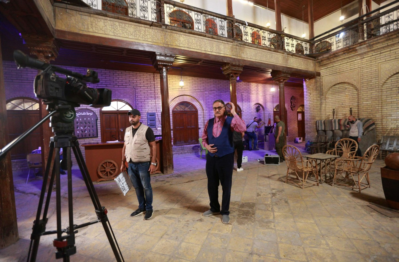 "Iraqi TV drama star Mahmoud Abu al-Abbas, center, and actors prepare to perform their roles in ""The Hotel, at a filming location in Baghdad, Iraq. (AP)"