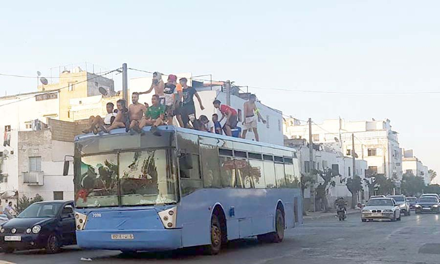 Passengers sit on top of an overcrowded bus in Casablanca. (Saad Guerraoui)