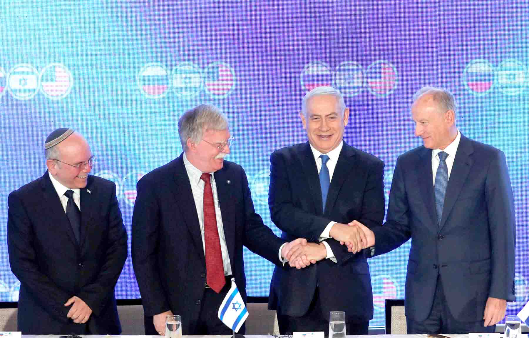 Israeli Prime Minister Binyamin Netanyahu shakes hands with US national security adviser John Bolton and Nikolai Patrushev, secretary of the Russian Security Council, as Israeli national security adviser Meir Ben-Shabbat stands nearby during opening statements of a trilateral meeting between American, Israeli and Russian top security advisers in Jerusalem June 25, 2019. (Reuters)