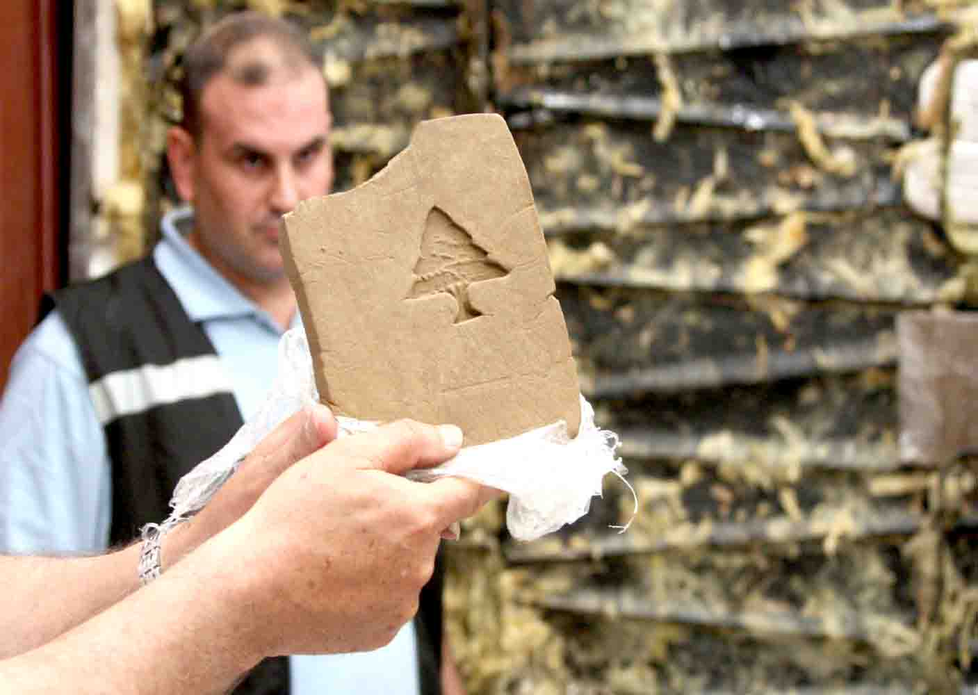 Harsh measures. A Lebanese customs officer shows a confiscated block of hashish in Beirut.(AFP)
