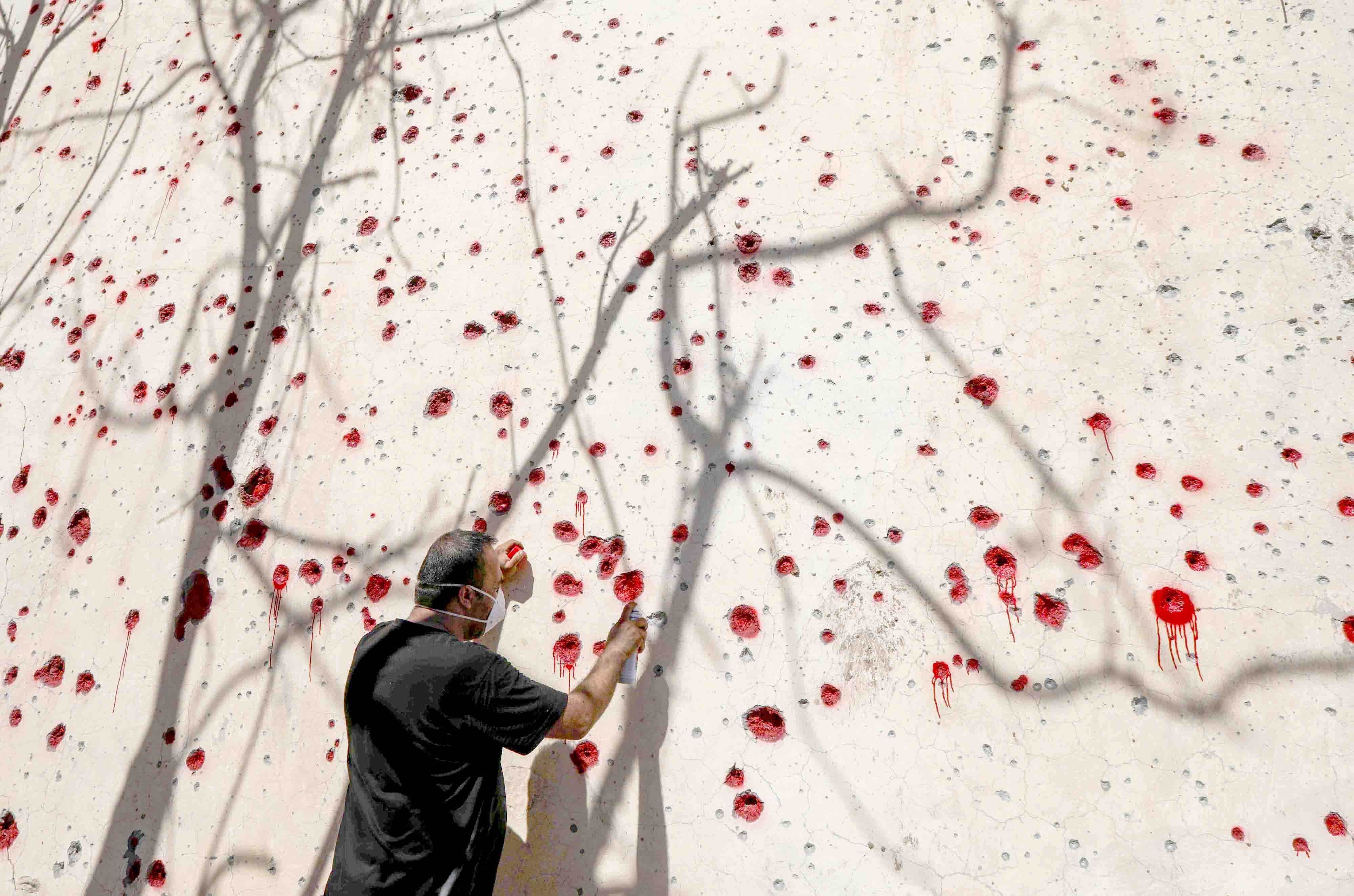 Deafening silence. A Kurdish man sprays red paint at holes in a wall made by shrapnel from an IRGC rocket attack in Koysinjaq, 100km east of Erbil, last September.(AFP)