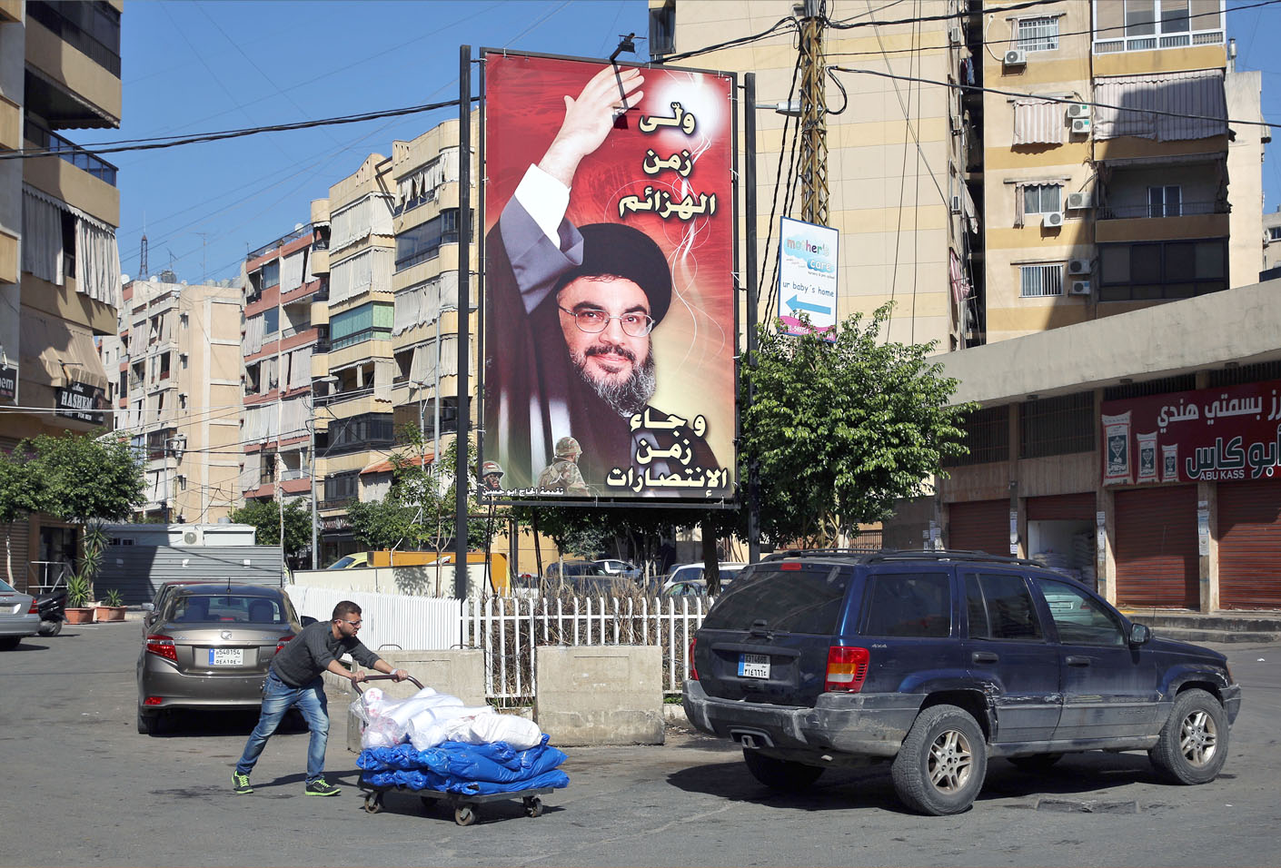 A man pushes a trolley as he passes a poster showing Hezbollah leader Sayyed Hassan Nasrallah in the southern suburb of Beirut. (AP)
