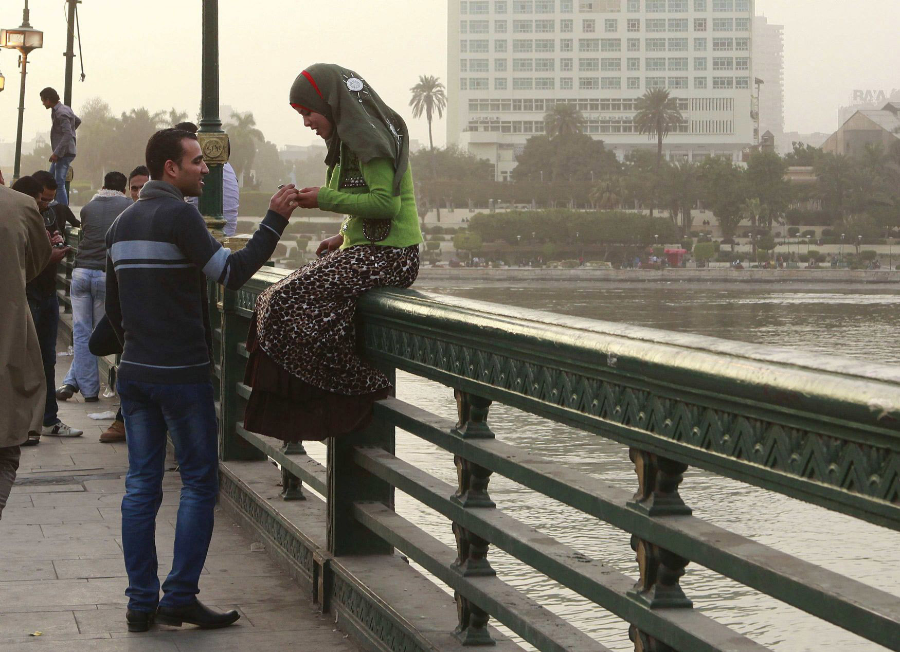 A couple talks on a bridge in central Cairo.  (Reuters)