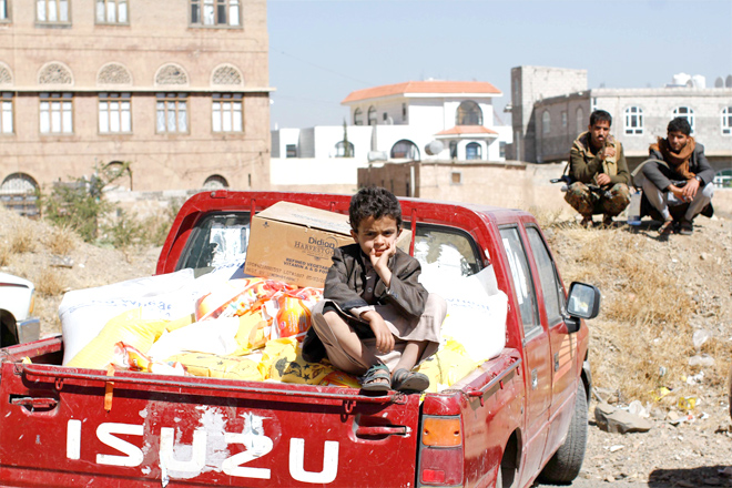 Firm grip on Yemenis' lives. A son of a Houthi supporter sits on the back of a truck with food aid in Sana'a. (Reuters)
