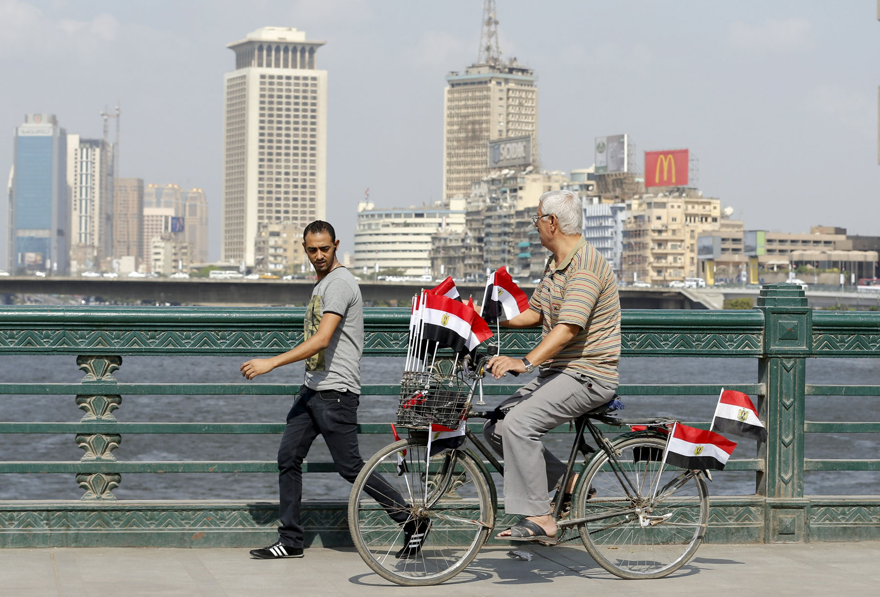 A man rides a bicycle decorated with Egyptian national flags at Qasr al-Nil bridge in Cairo. (Reuters)