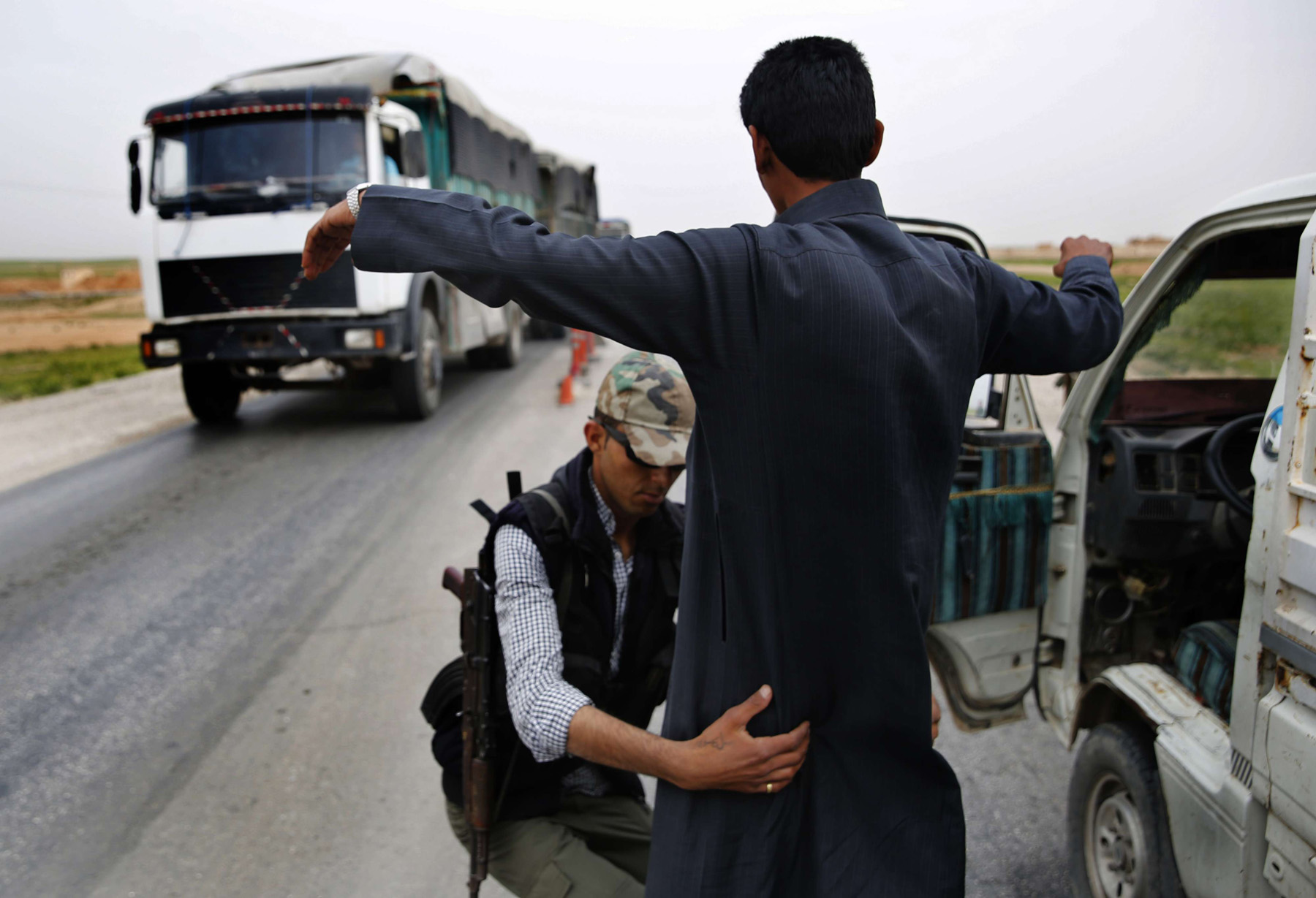 Stubborn concerns. A Kurdish policeman searches a man at a checkpoint controlled by US-backed Syrian Democratic Forces on a highway in Hasakah province.  (AP)