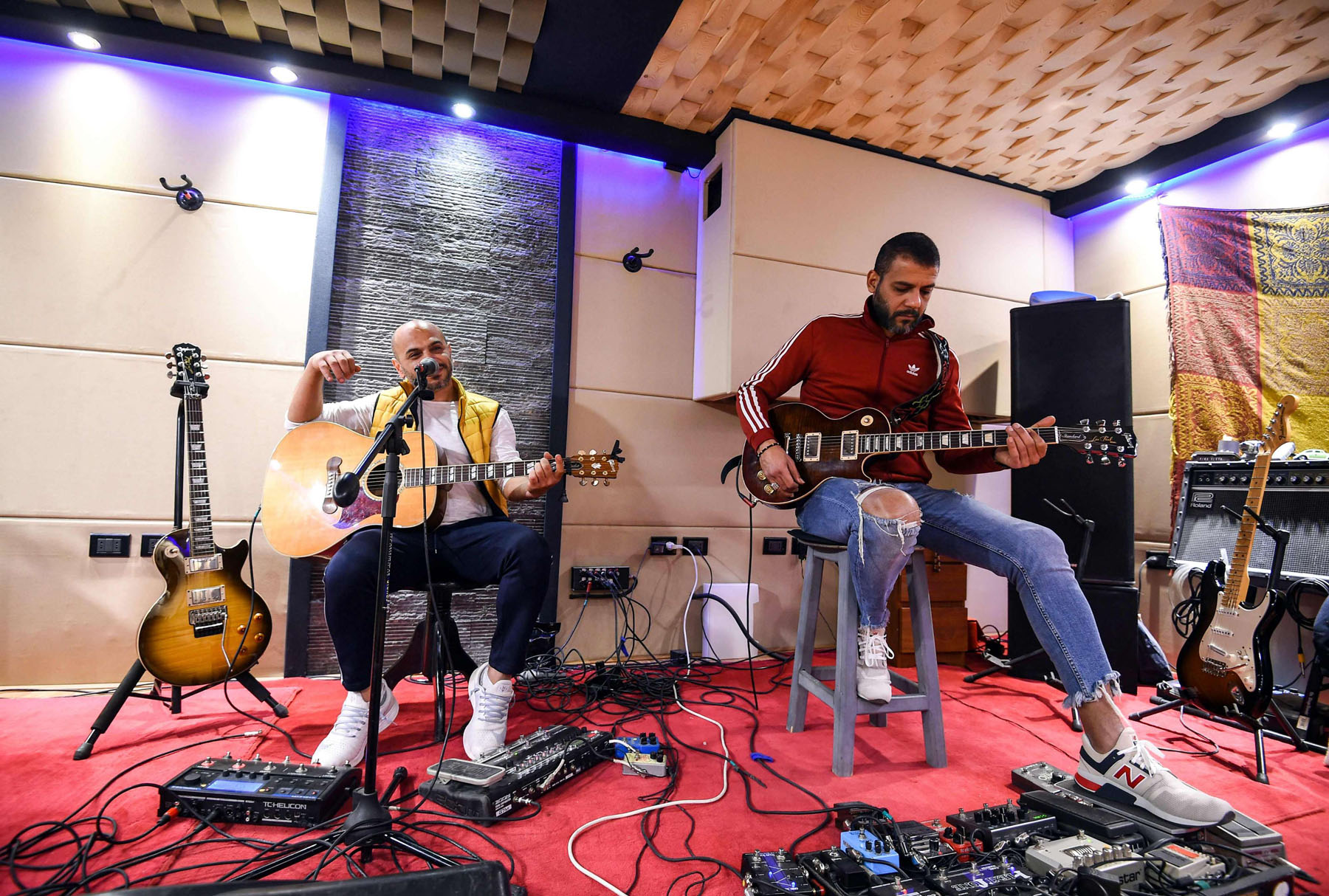 Hani El Dakkak (L), lead singer and guitarist, and Mahmoud Siam, guitarist for Egyptian rock band Massar Egbari, warm up in a recording studio in Cairo. 			    (AFP)